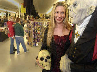 sales clerk april kassarjian sports a gothic vampire costume and stands next to a full