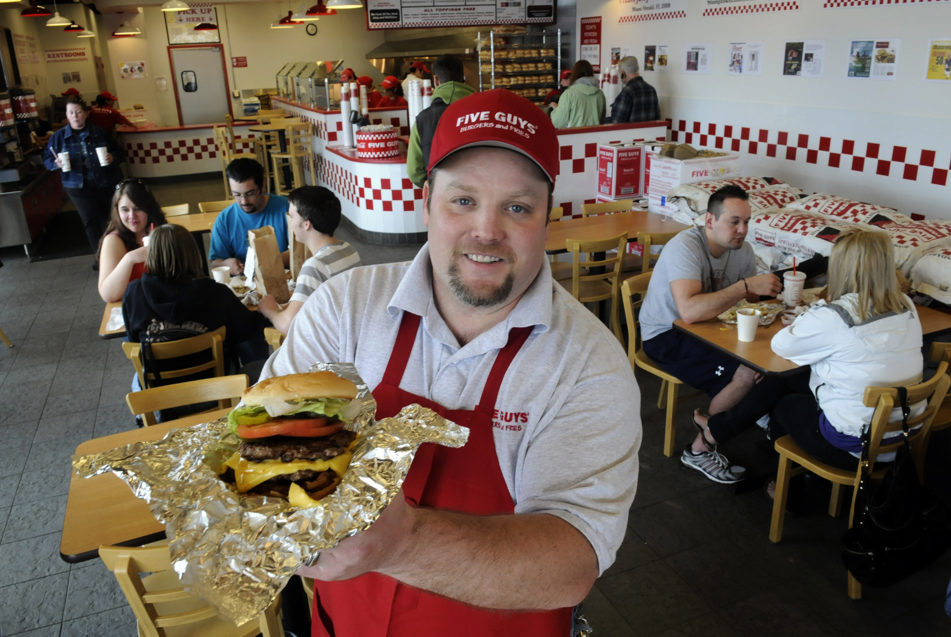 Five Guys Burgers And Fries General Manager Ron Cerhet Shows Off A Bacon Cheeseburger At Their