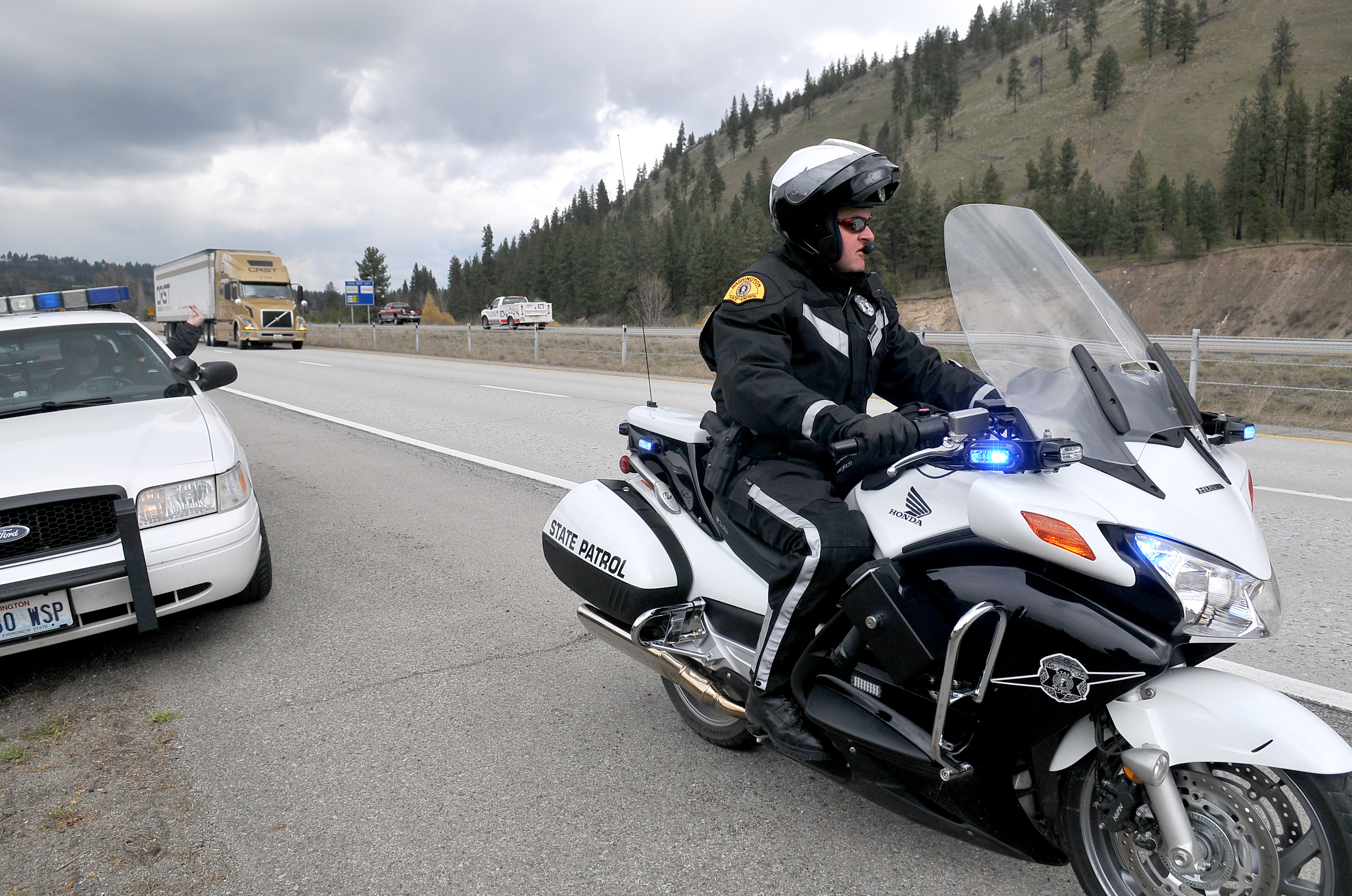 Washington State Trooper Jeff Sevigney Waits On A New Honda Motorcycle For Truck To Pass