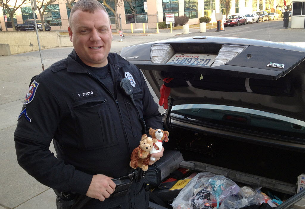 a5ecee55288 Spokane police patrol officer Ryan Snider holds two of the 1