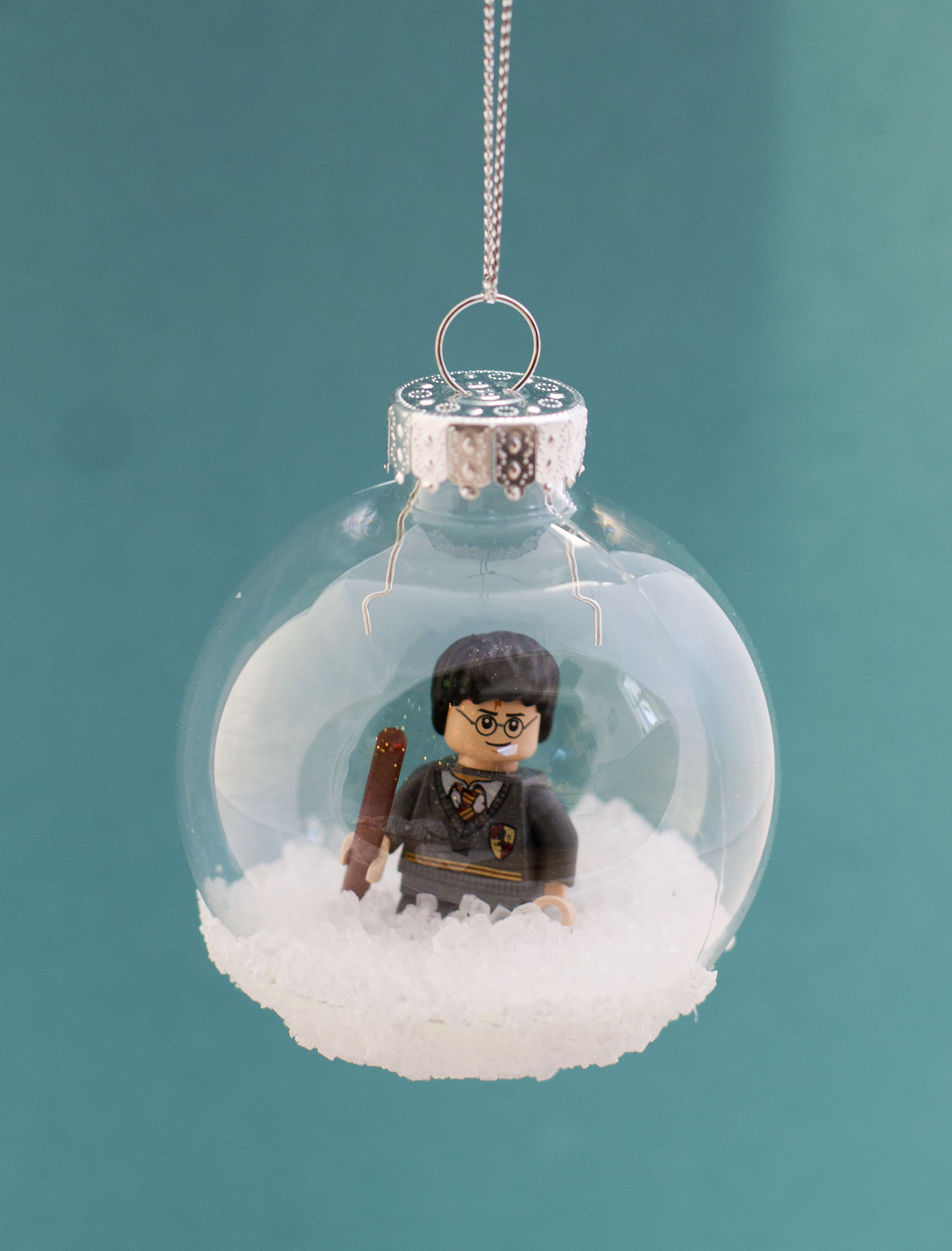 A Harry Potter Lego minifigure enclosed in a plastic Christmas tree ornament bulb. The bulb