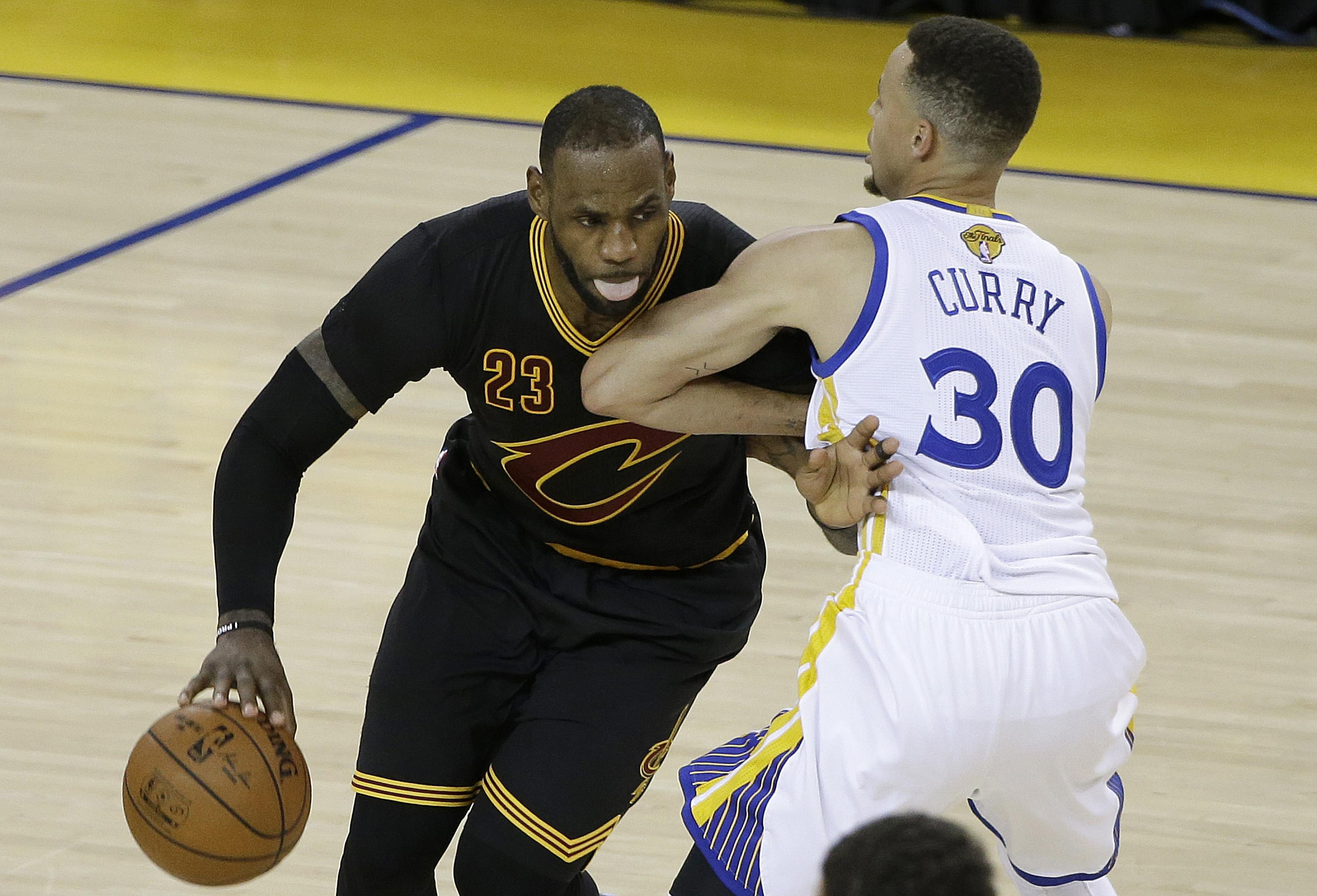 924483cae4cd Cleveland Cavaliers forward LeBron James dribbles against Golden State  Warriors guard Stephen Curry during the second