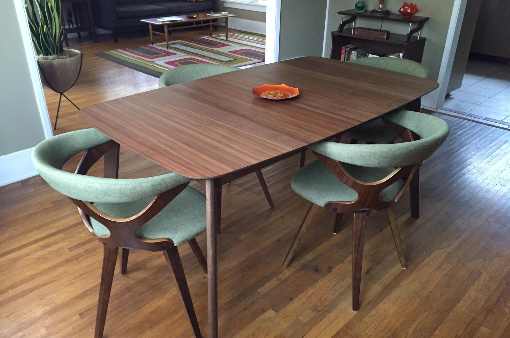 A mid century modern inspired dining room table and chairs fit the style of a