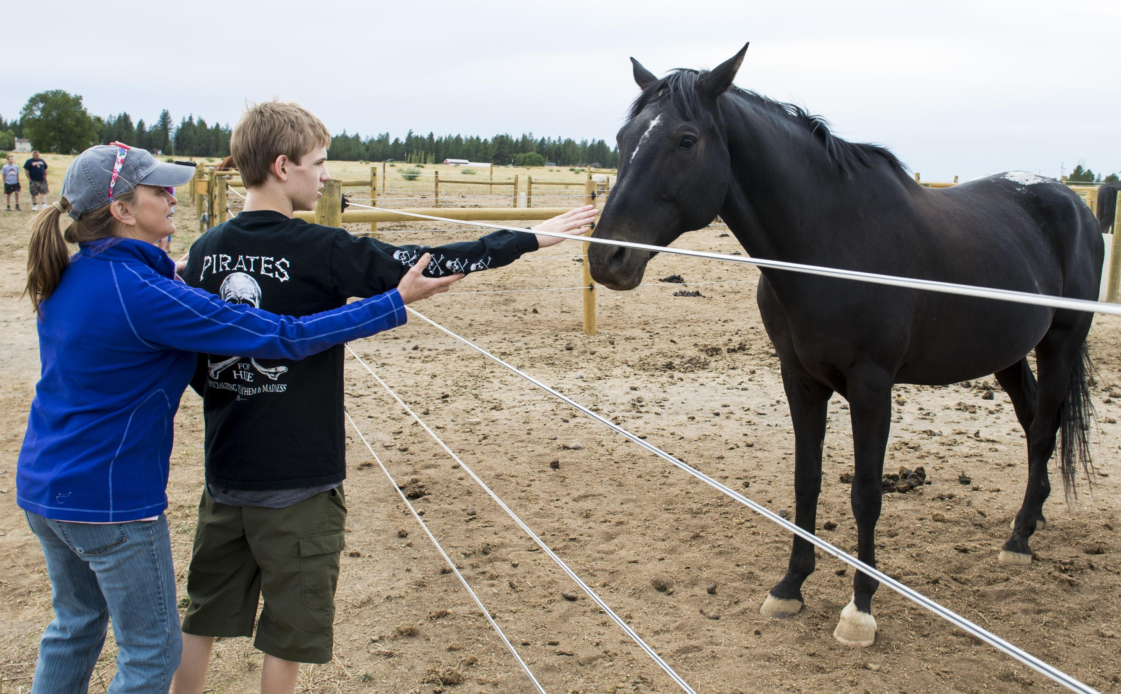 Free rein therapeutic riding makes home at spokane equestrian center during an open house free rein volunteer linda carney helps trevin hansen 14 m4hsunfo