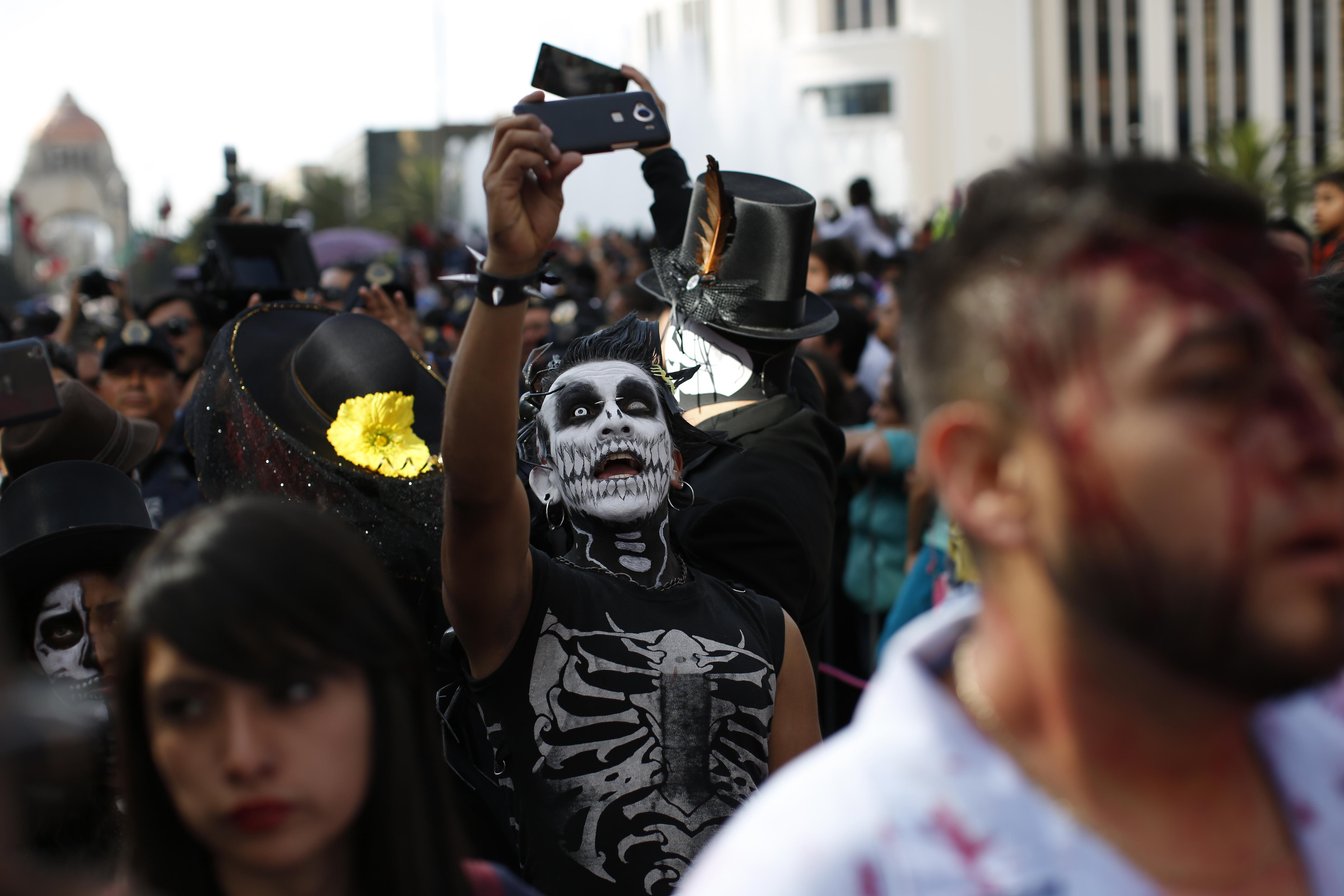 a man in costume takes a selfie during a day of the dead parade along mexico