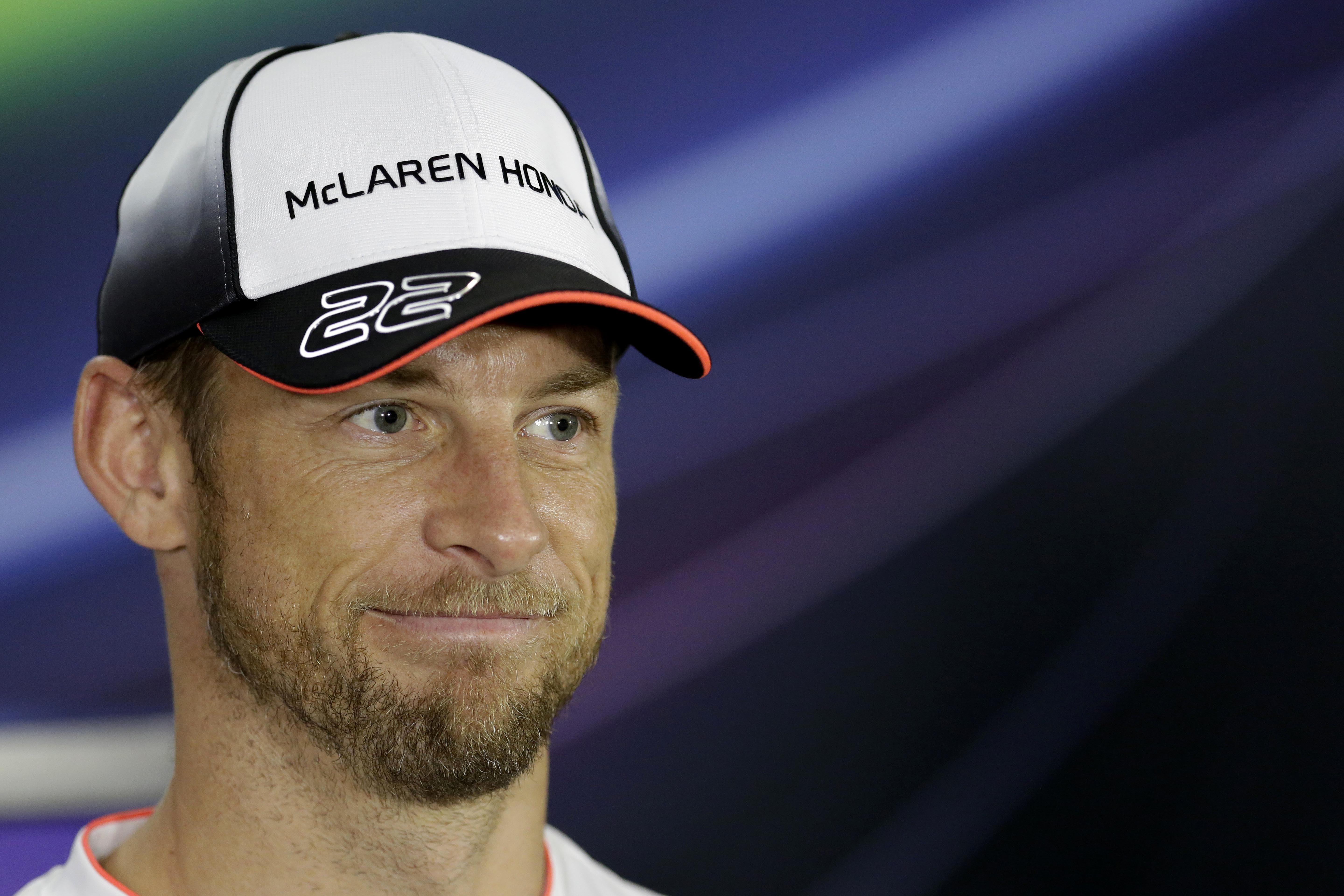 553eef187b630 McLaren driver Jenson Button of Britain reacts during a news conference at  the Yas Marina racetrack