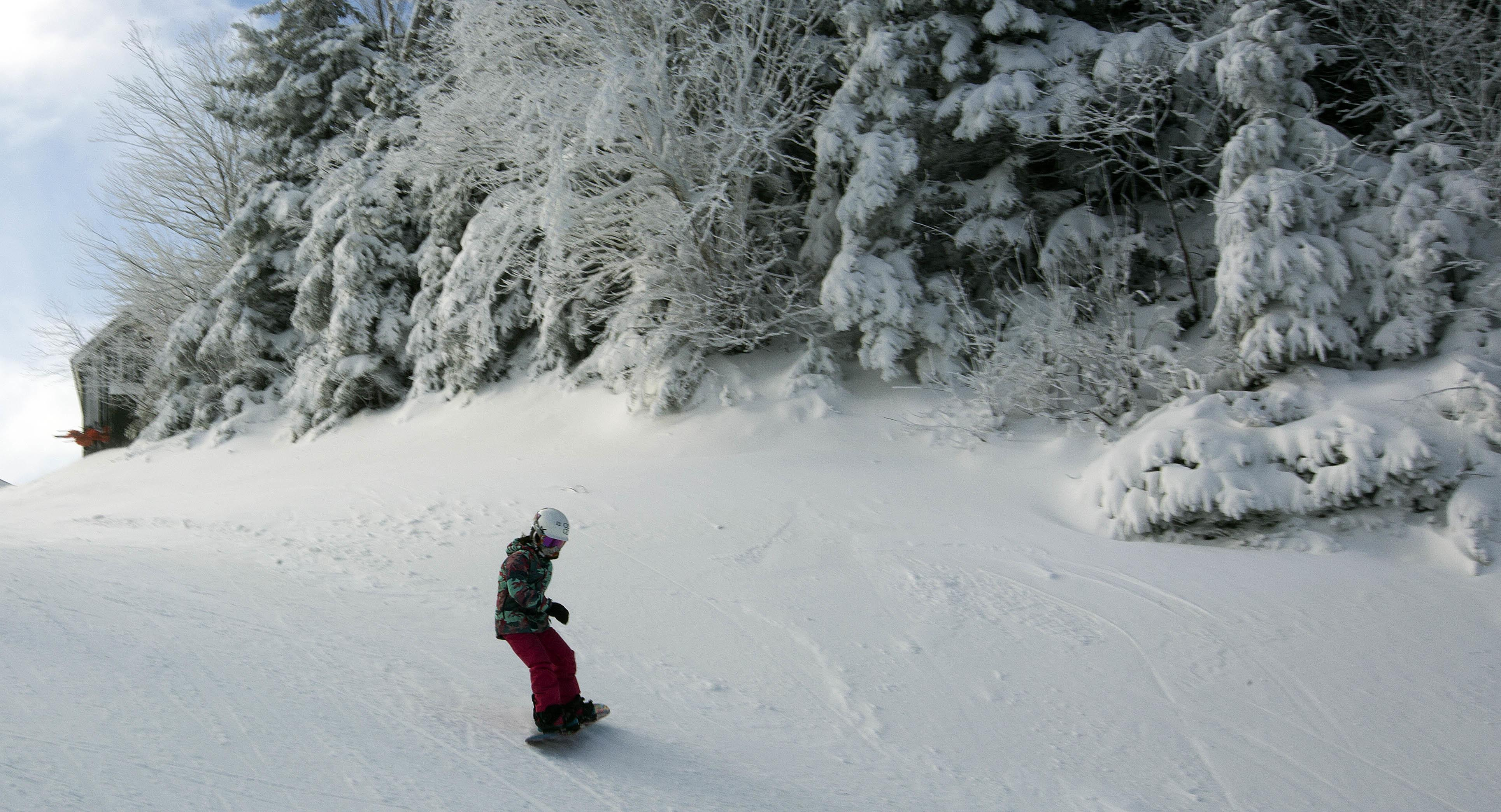 c031ce1a46c2 A young snowboarder takes the first run of the season on top of the  mountain on