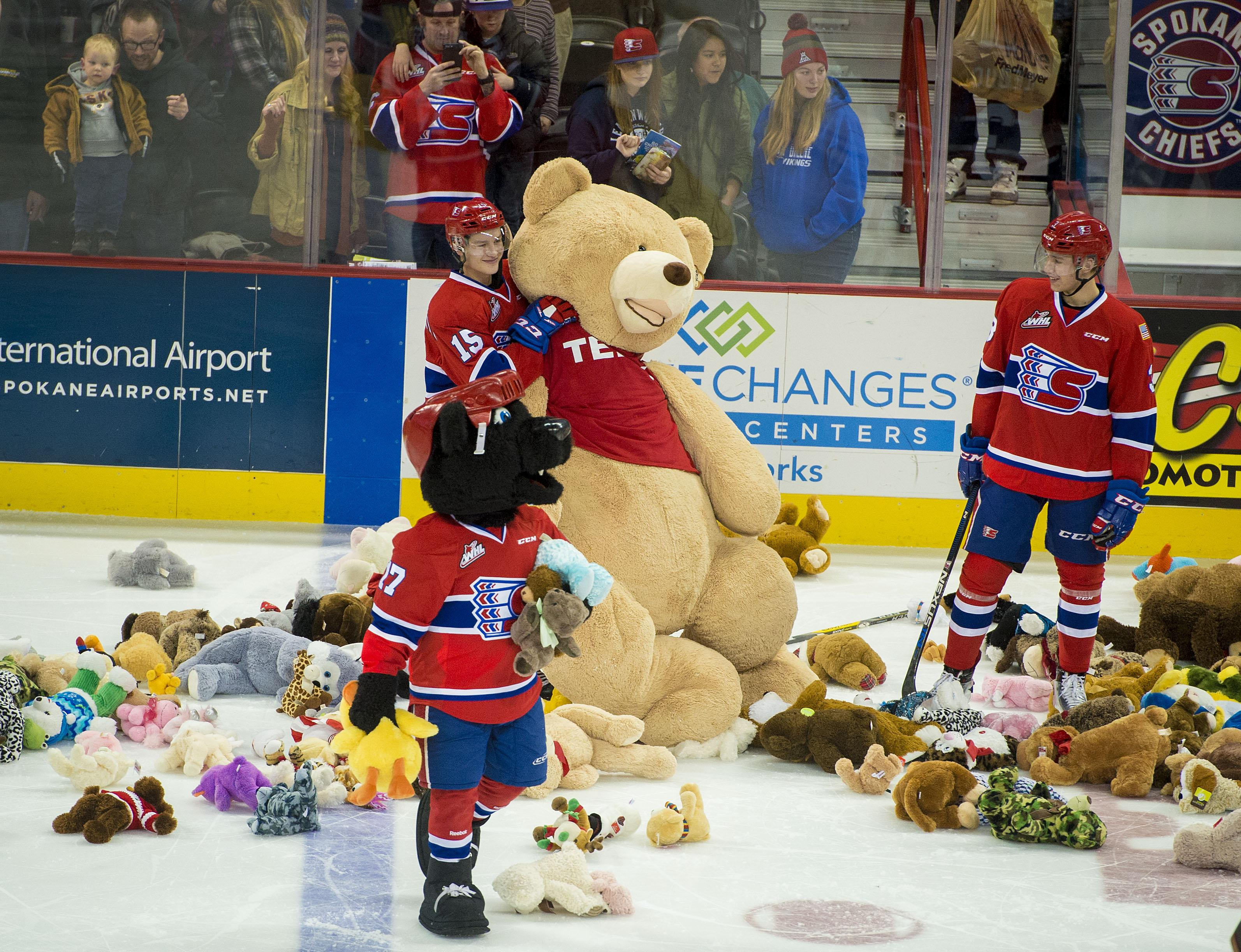members of the spokane chiefs collect stuffed animals thrown on the ice during their game friday