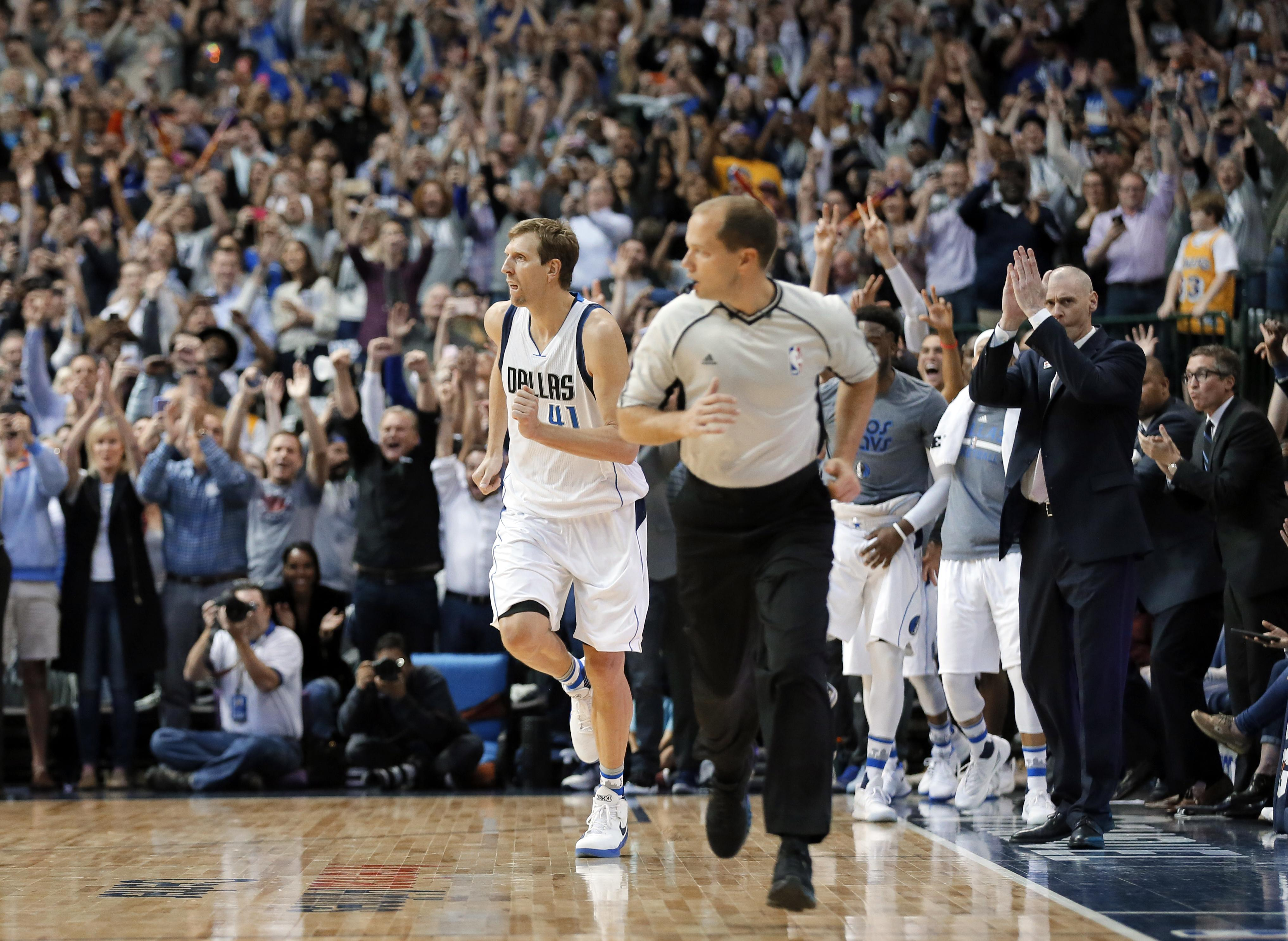 6861c336b Fans stand and cheer after Dirk Nowitzki (41) sunk a basket to reach his