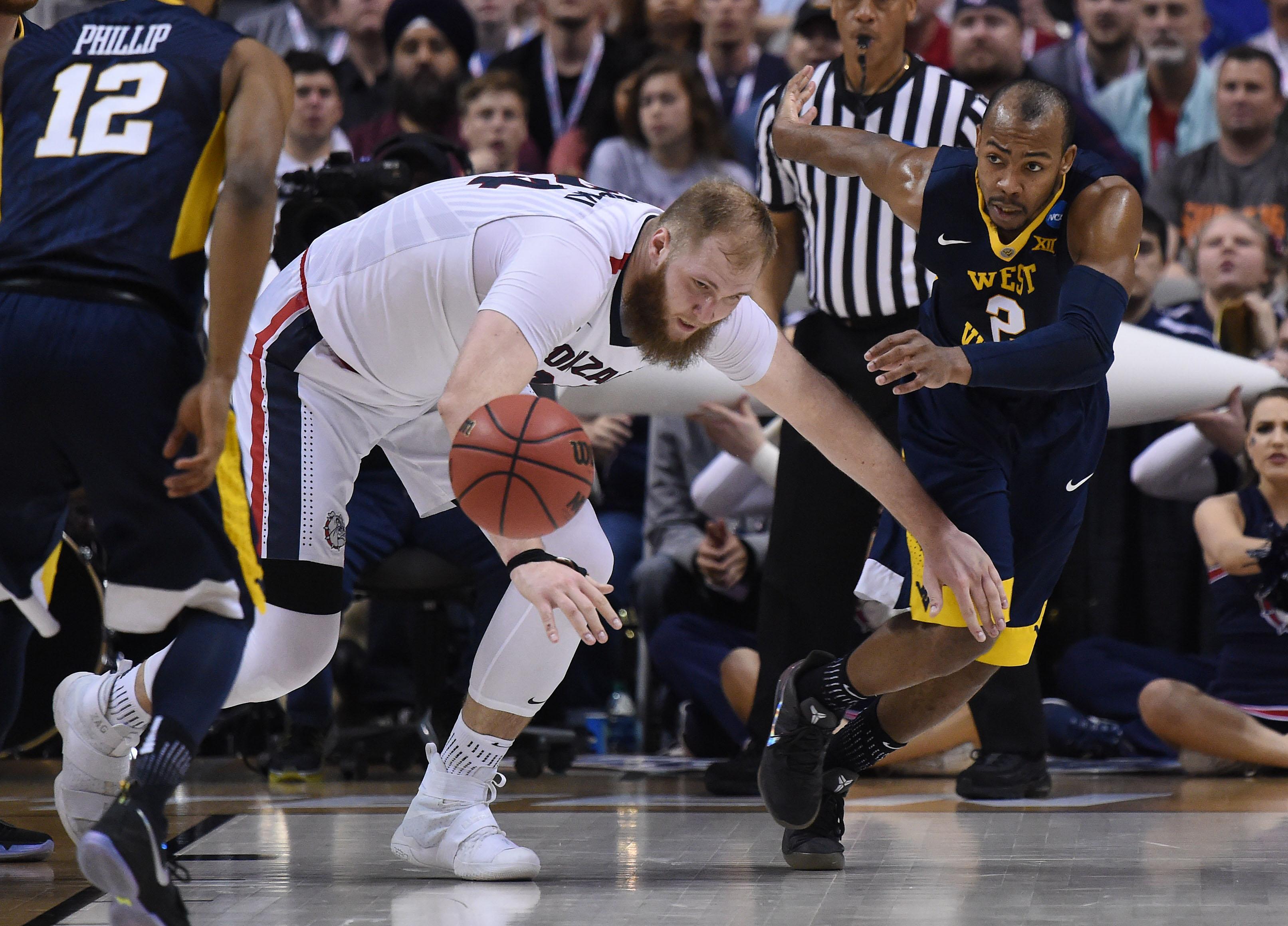 6b68e899390 Gonzaga center Przemek Karnowski (24) chases a loose ball with West  Virginia guard Jevon