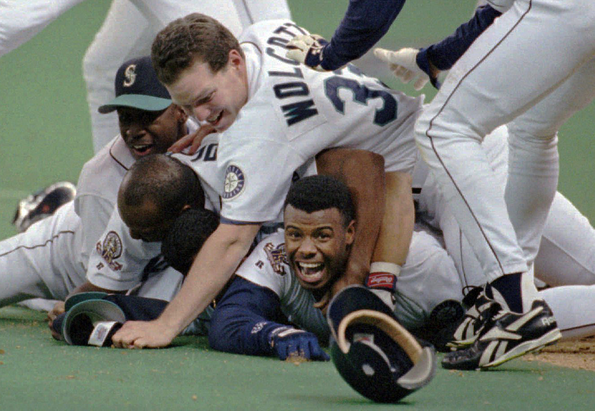 2abd5172cf Seattle Mariners' Ken Griffey Jr. smiles from beneath a pile of teammates  who mobbed