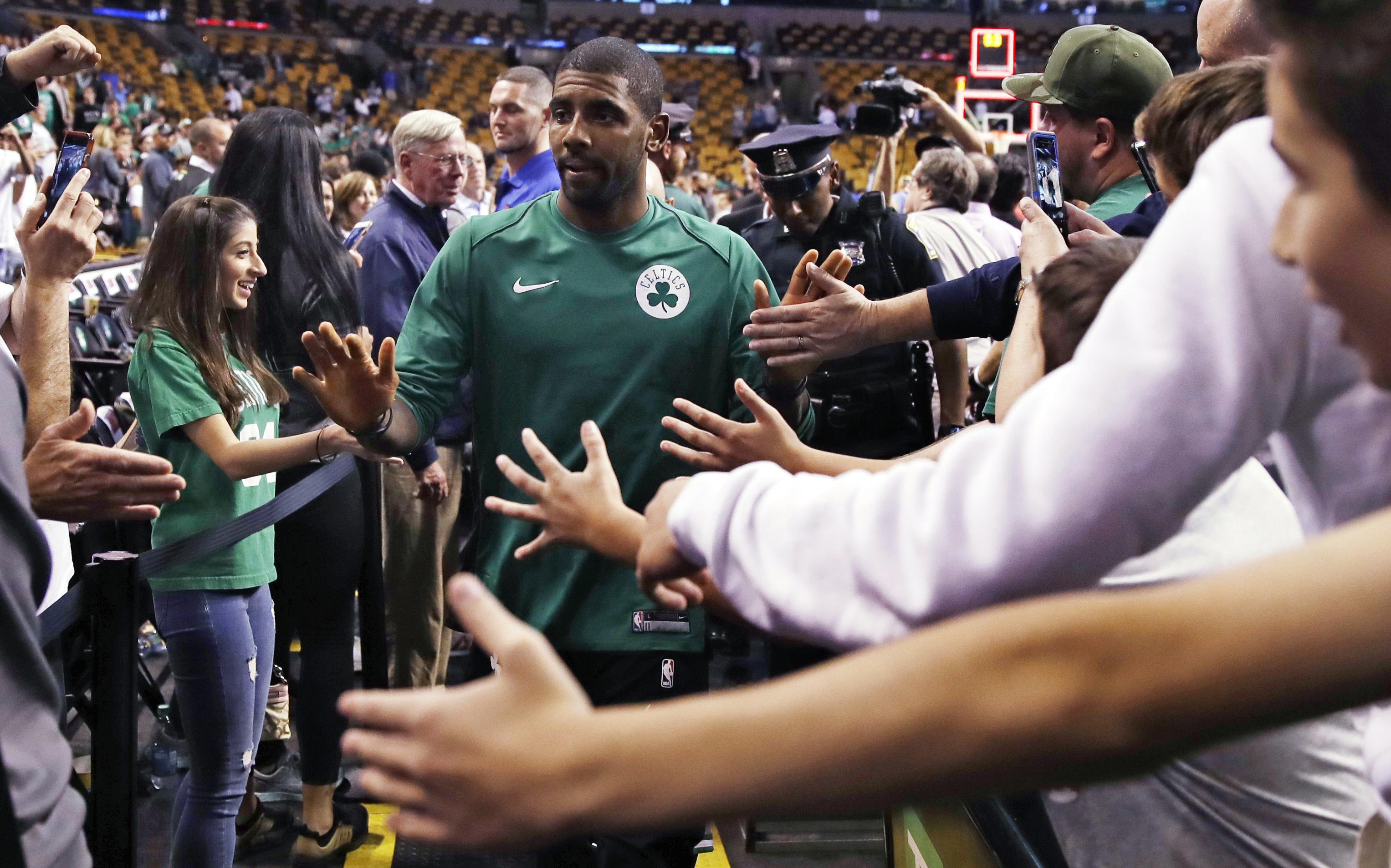 1465d1191874 Boston Celtics guard Kyrie Irving is greeted by fans after the team s NBA  preseason basketball game