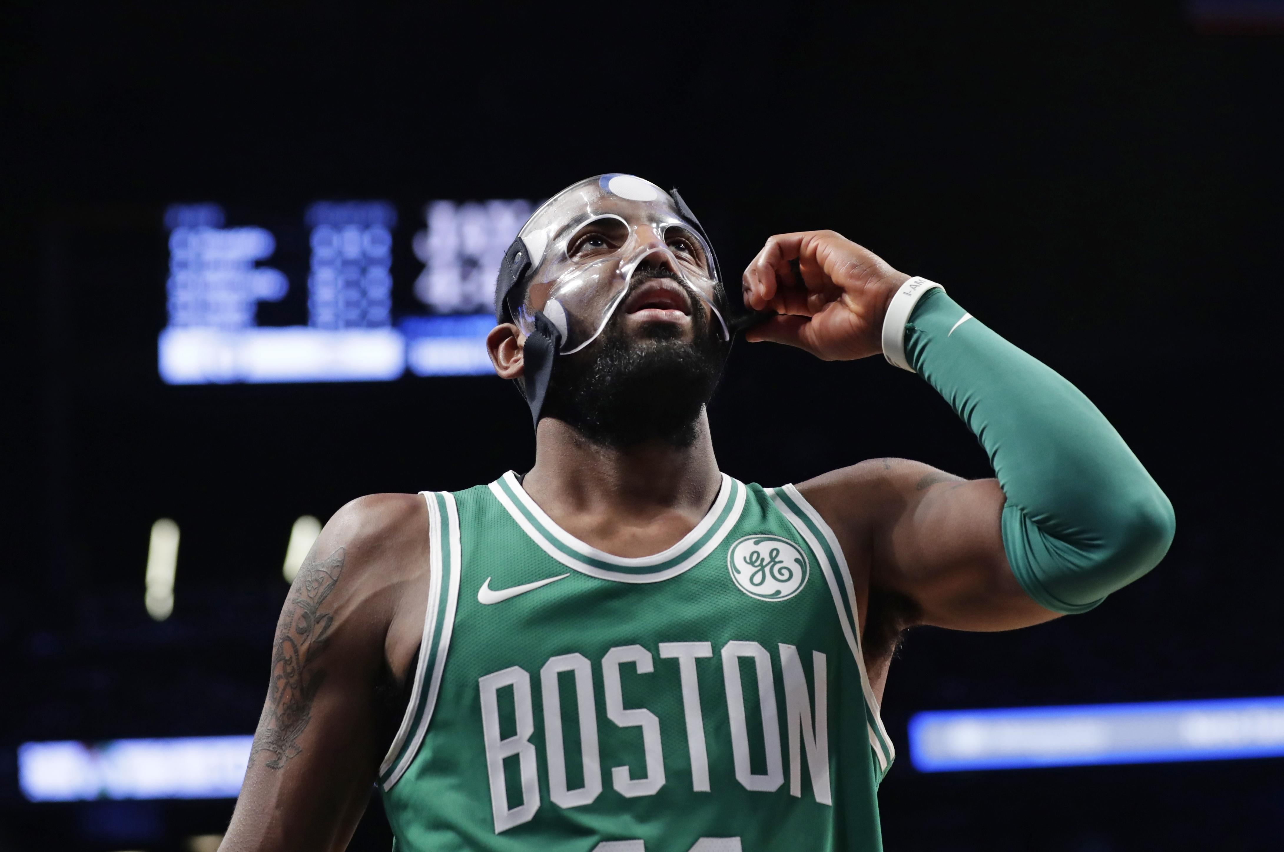 834f34833 Boston Celtics  Kyrie Irving (11) adjusts his mask during the second half of