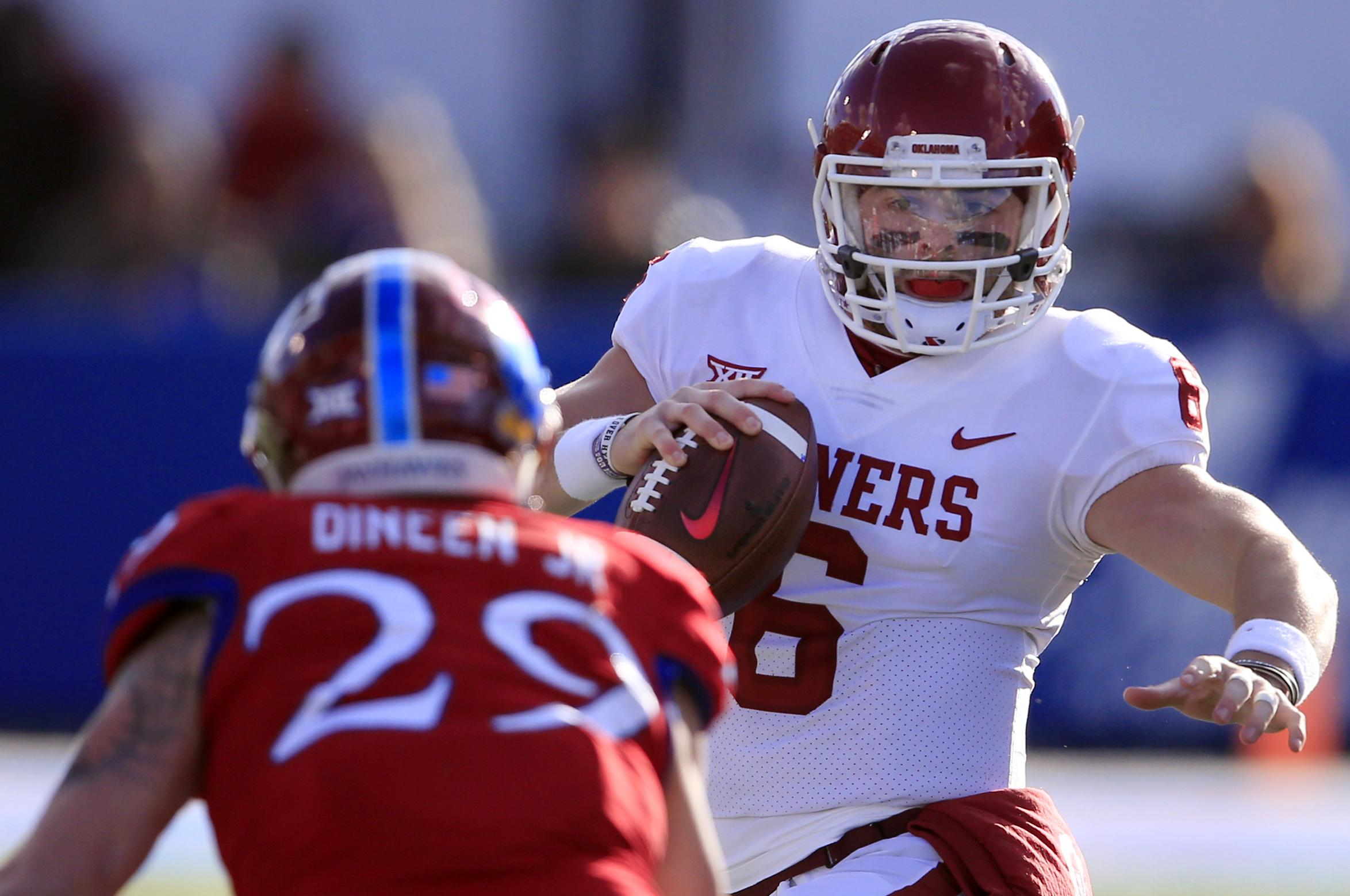 59368cf2 Oklahoma quarterback Baker Mayfield, right, tries to avoid Kansas  linebacker Joe Dineen Jr.