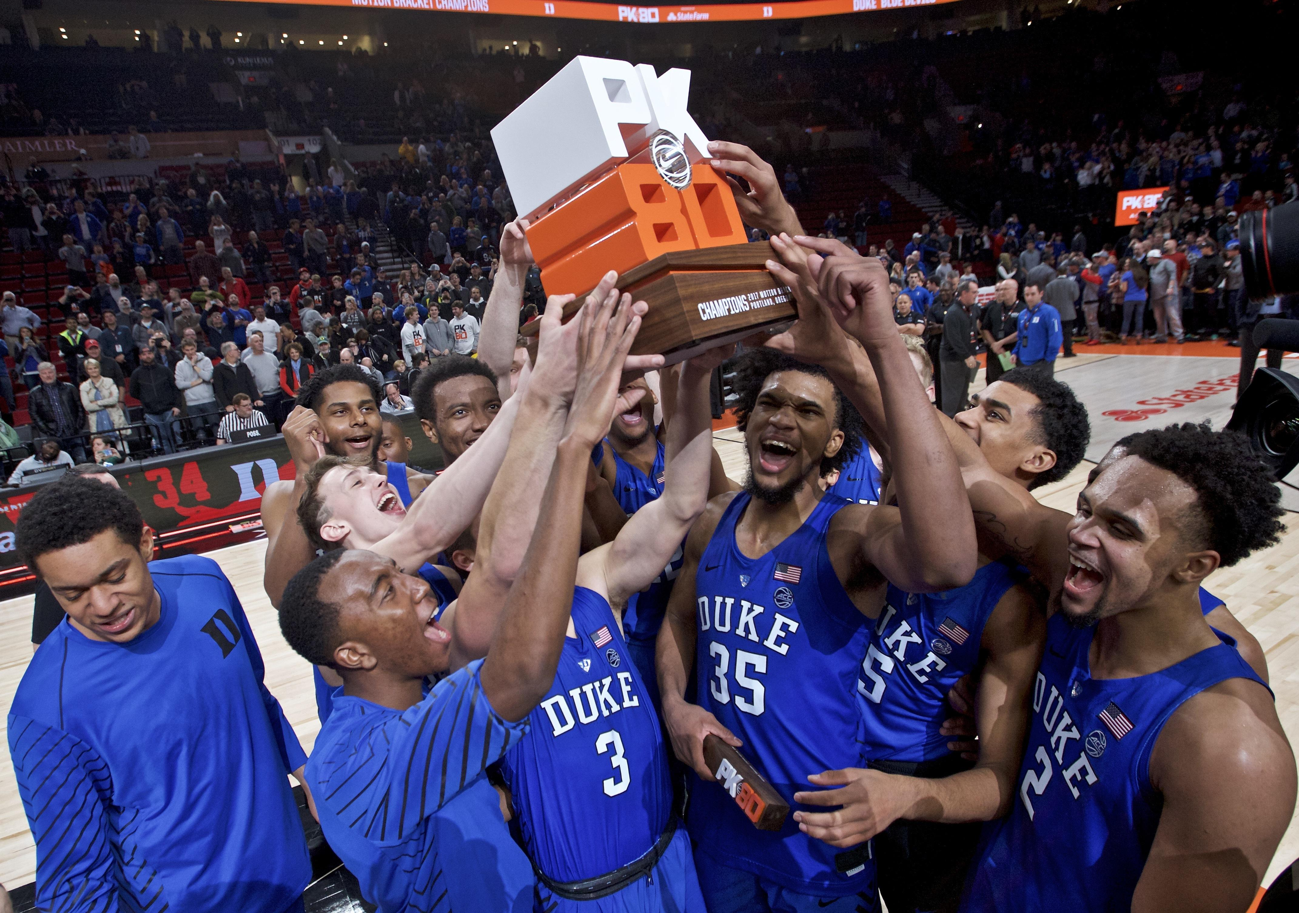 Duke holds up the championship trophy after an NCAA college basketball game against Florida in the