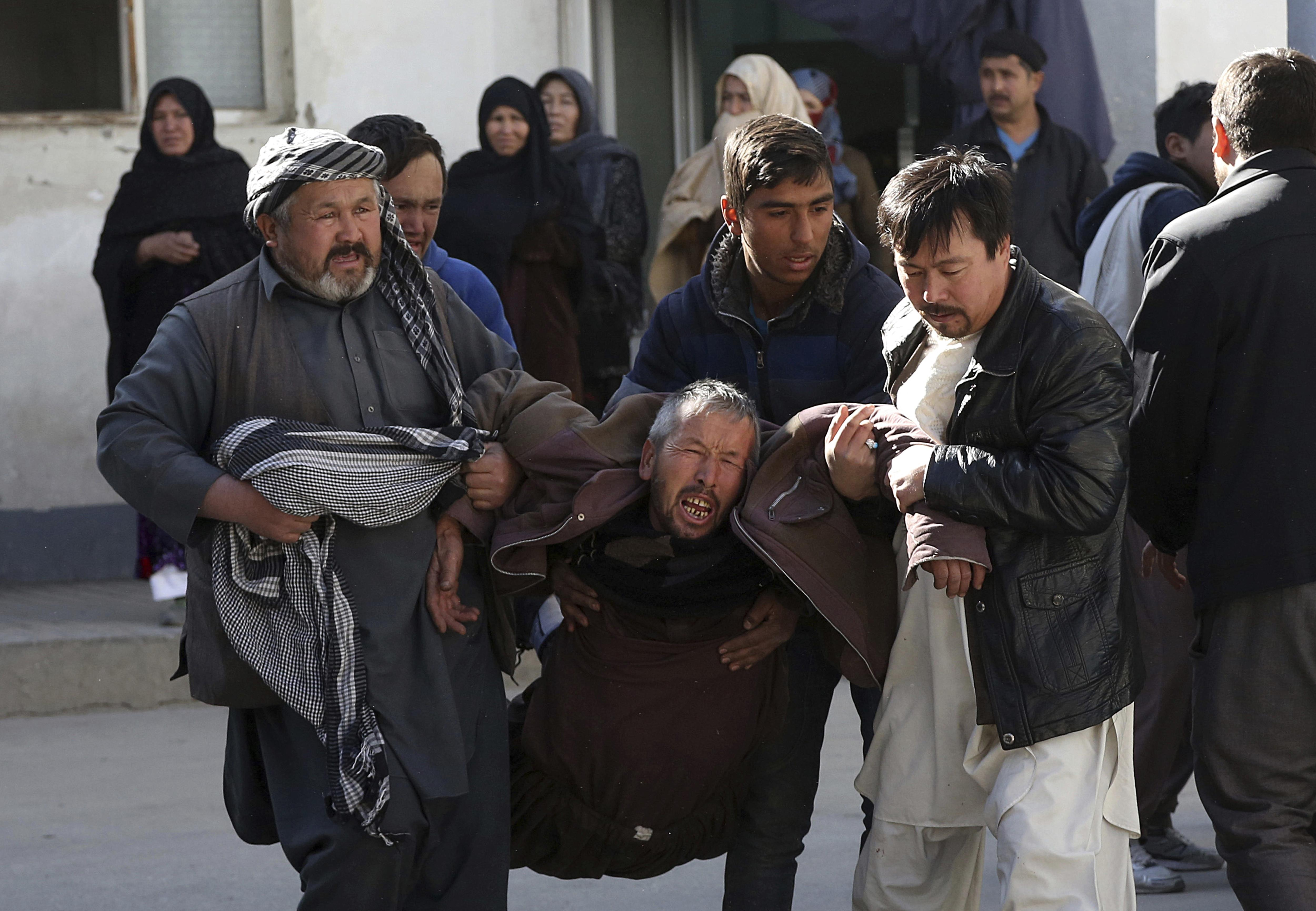 78f15165e704 A distraught man is carried following a suicide attack in Kabul