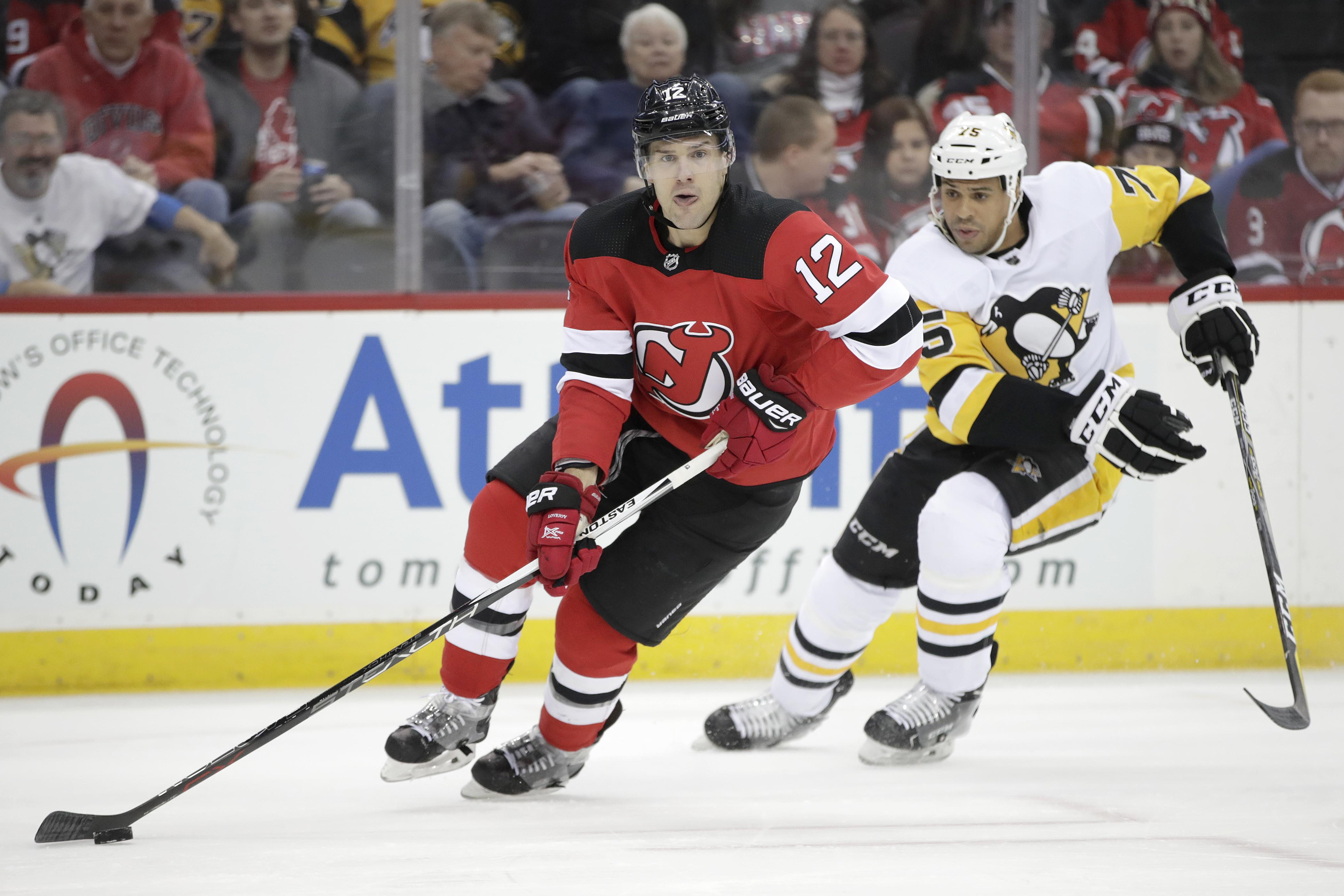 34de7c54e Devils defenseman Ben Lovejoy skates with the puck, trailed by Penguins  right wing Ryan Reaves