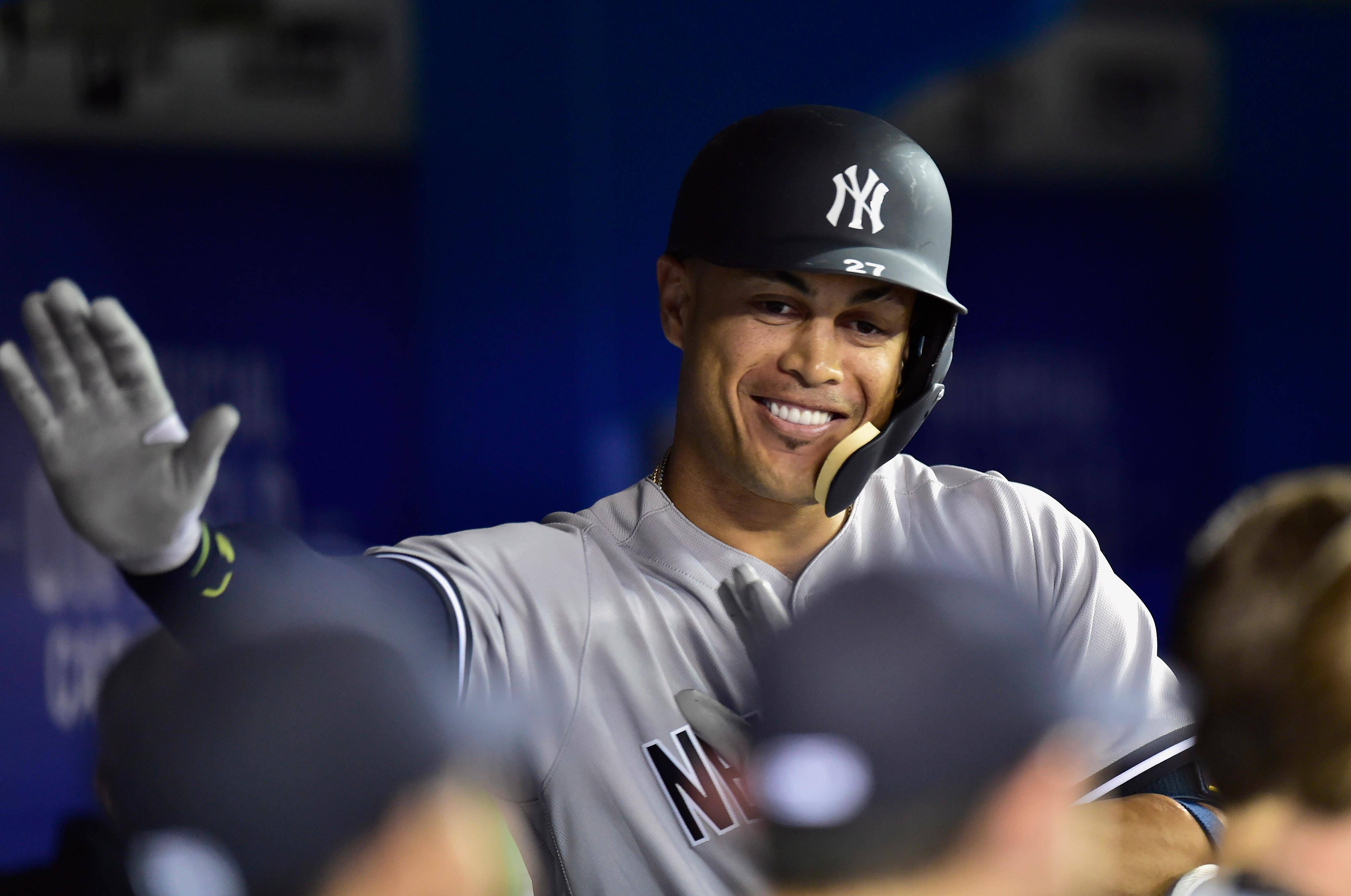 620af517f New York Yankees' Giancarlo Stanton celebrates his solo home run in the  dugout during the