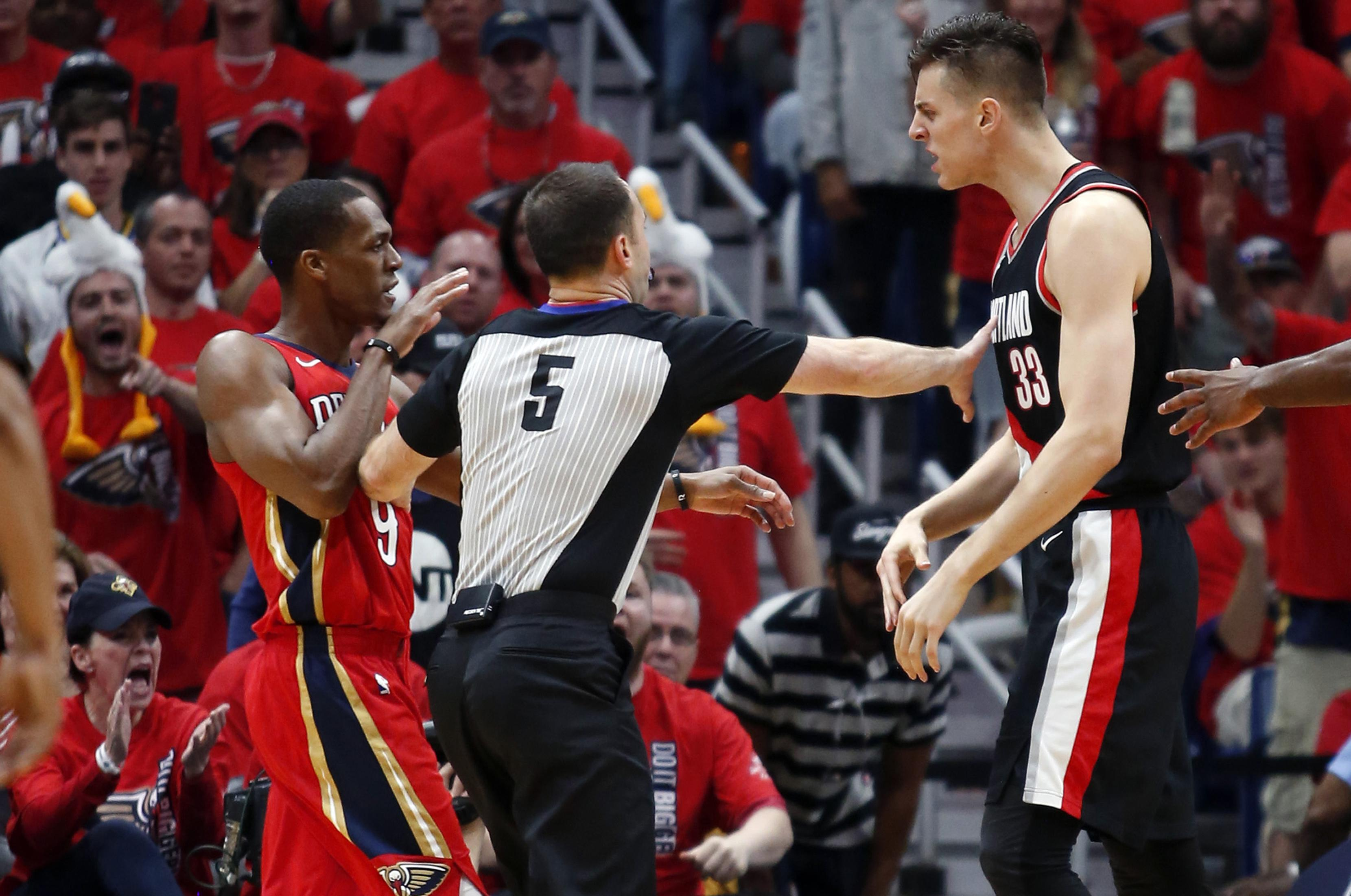 4f395557e An official separates Portland center Zach Collins and New Orleans guard  Rajon Rondo after a dust