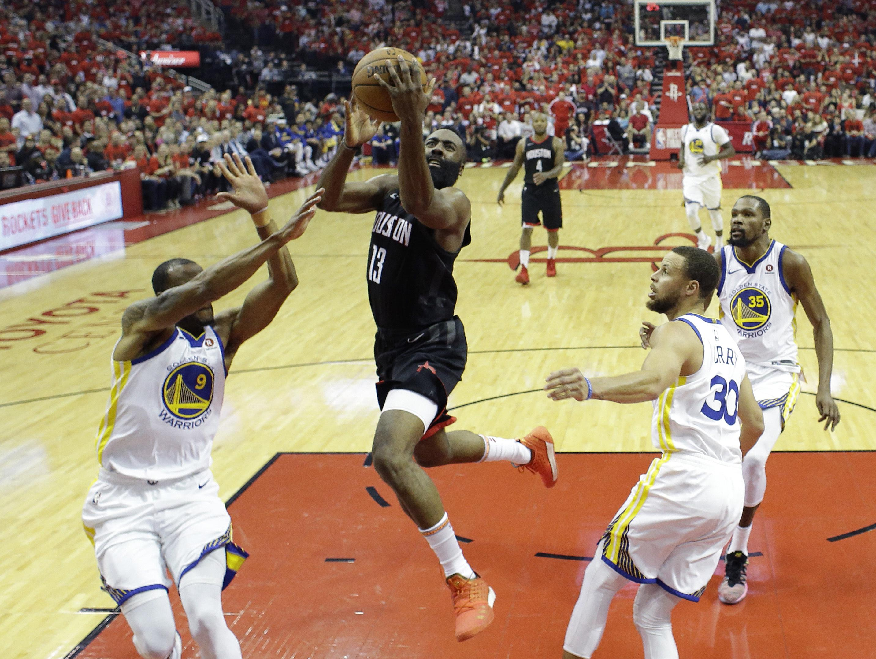 be7ebb3e511 Houston Rockets guard James Harden (13) drives to the basket past Golden  State Warriors