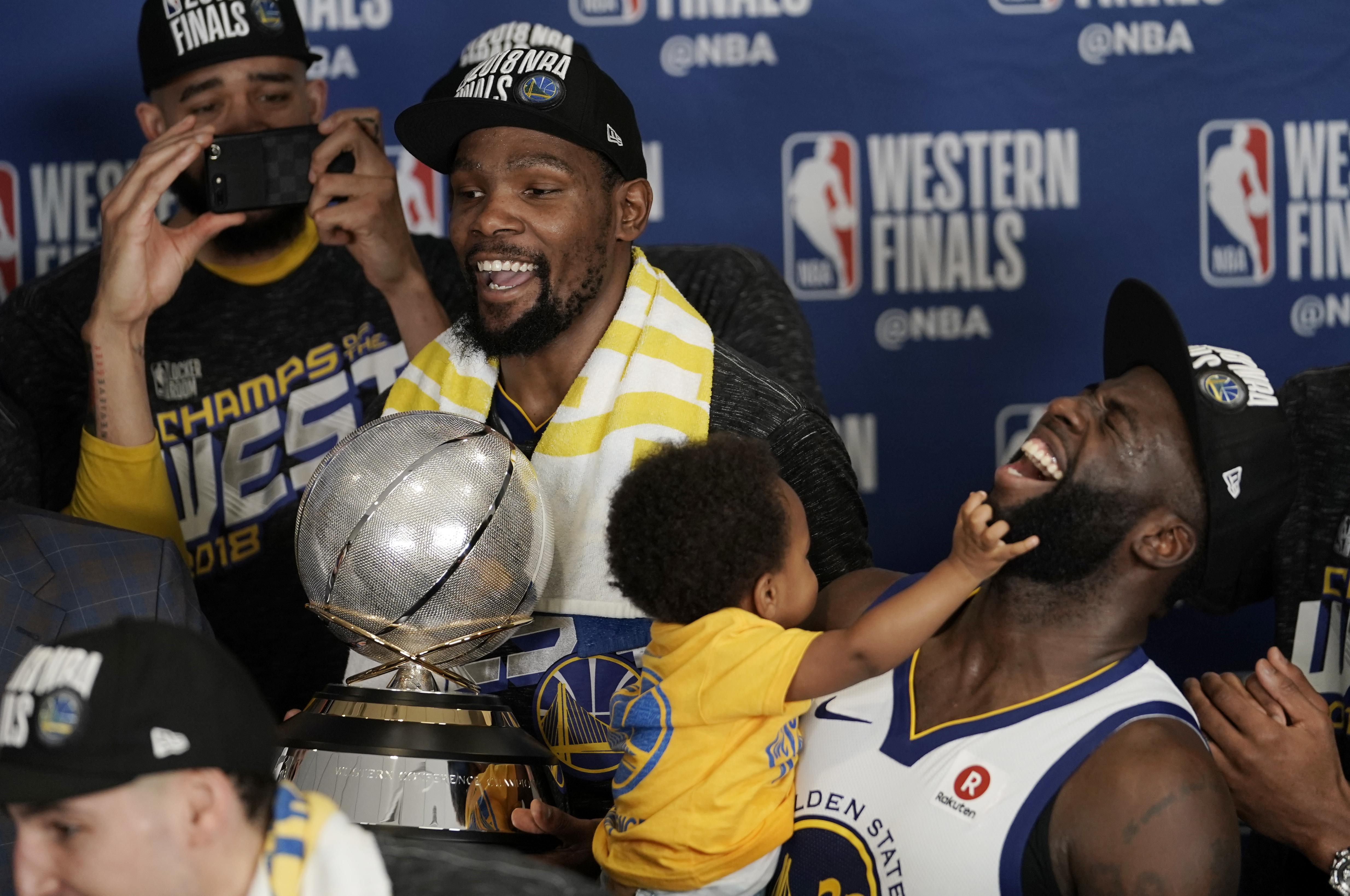 d5e6cbecf628 Golden State Warriors forward Kevin Durant holds the trophy as he and  teammate Draymond Green