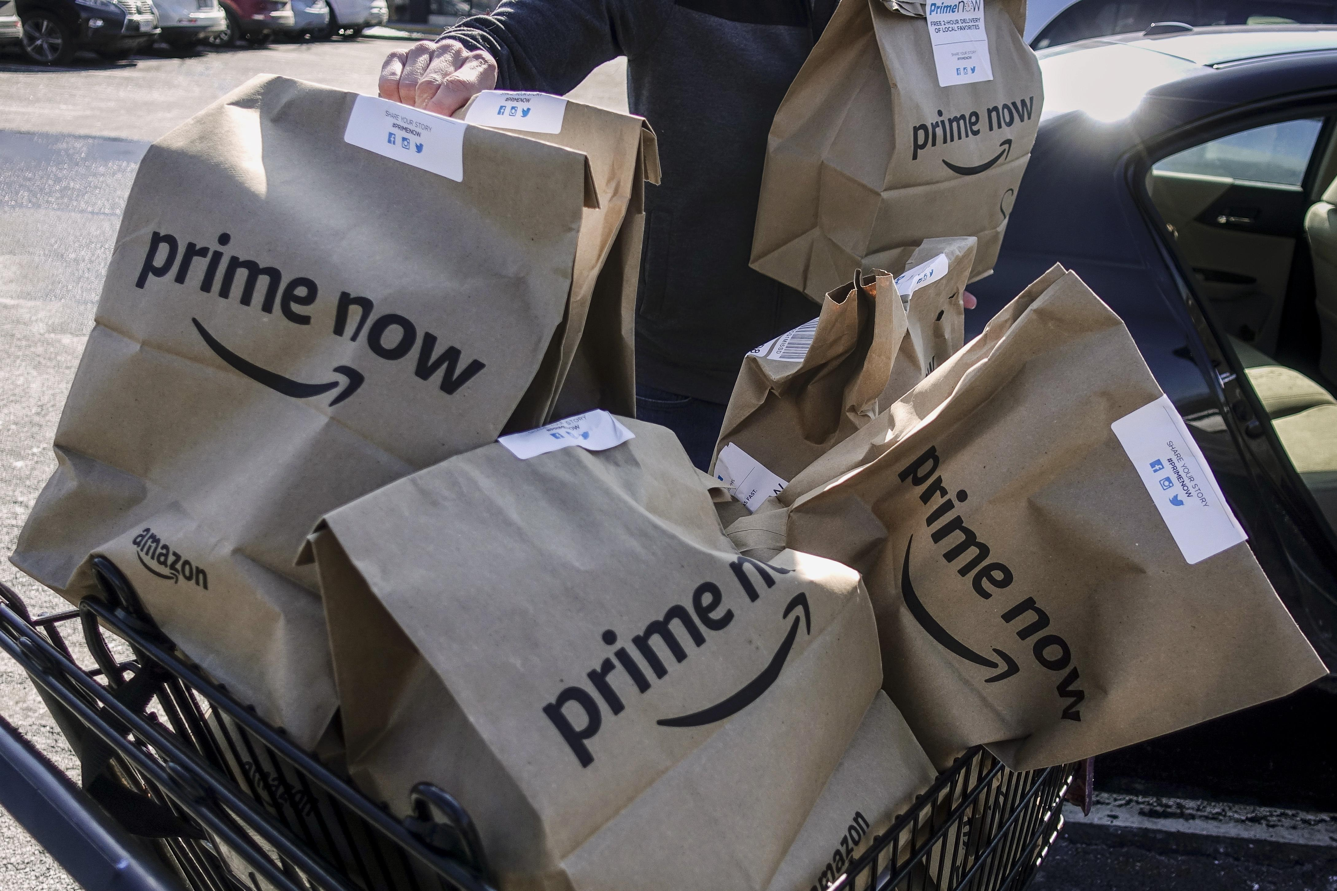 186cfa3b6bc Amazon Prime Now bags full of groceries are loaded for delivery by a  part-time