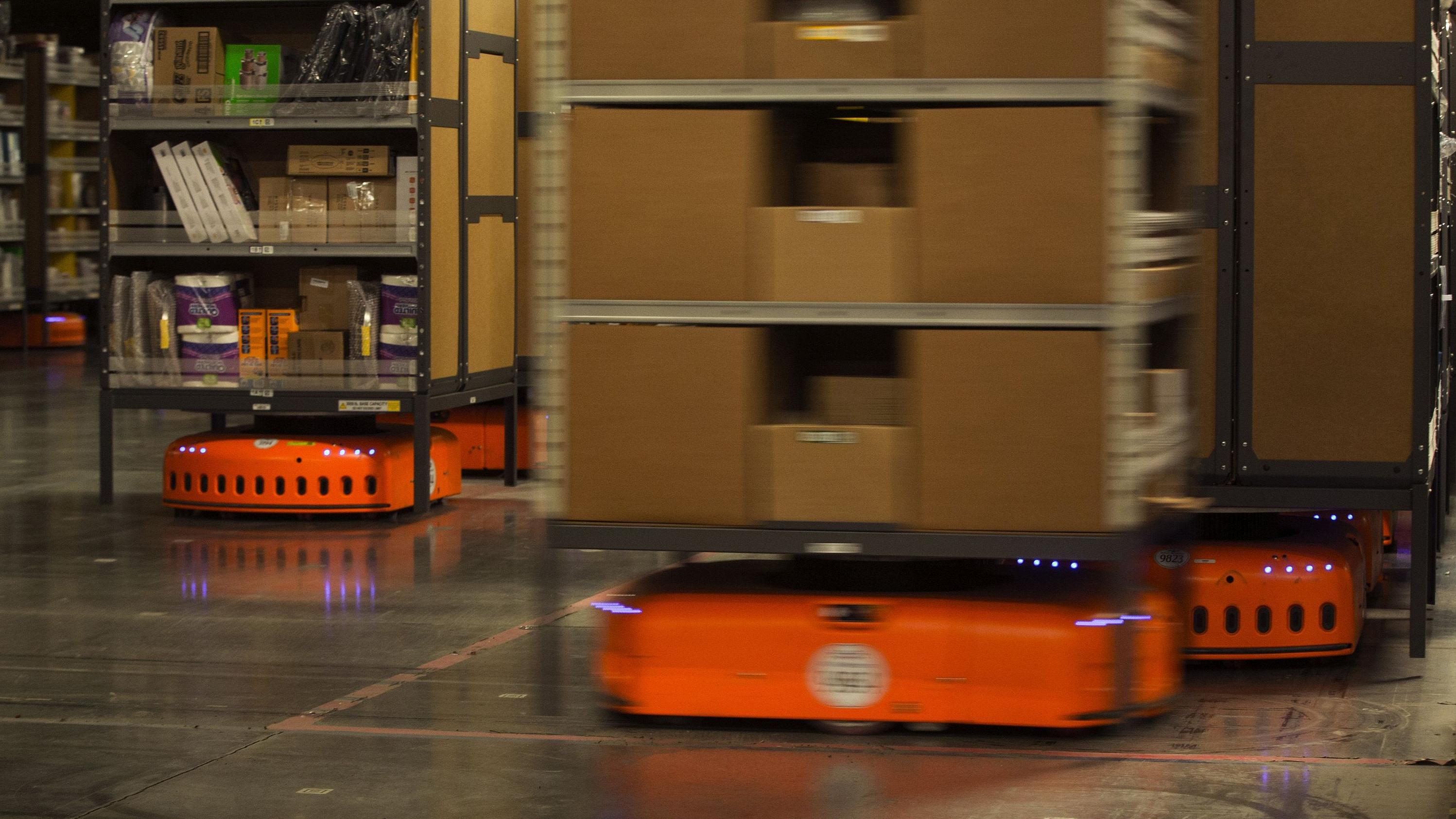 KIVAs, Amazon robots that are used to move items around the Amazon fulfillment center in DuPont, Wash., scurry by as they move merchandise. The KIVAs weigh 800 pounds each and can carry up to 3,000 pounds of merchandise. (Ellen M. Banner / TNS)