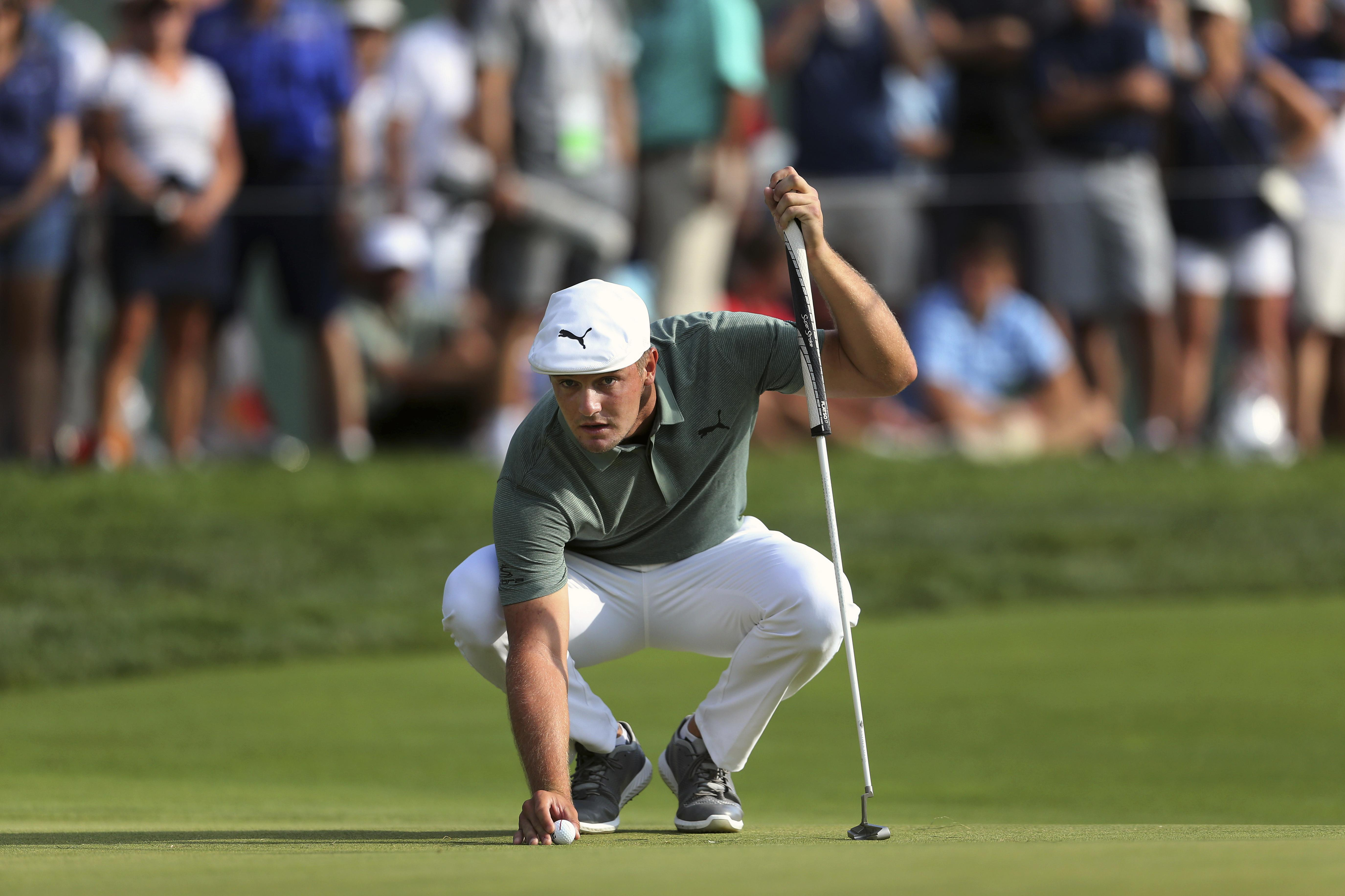 b8c36b6d Bryson DeChambeau eyes his putt as he places his ball on the green at the  18th