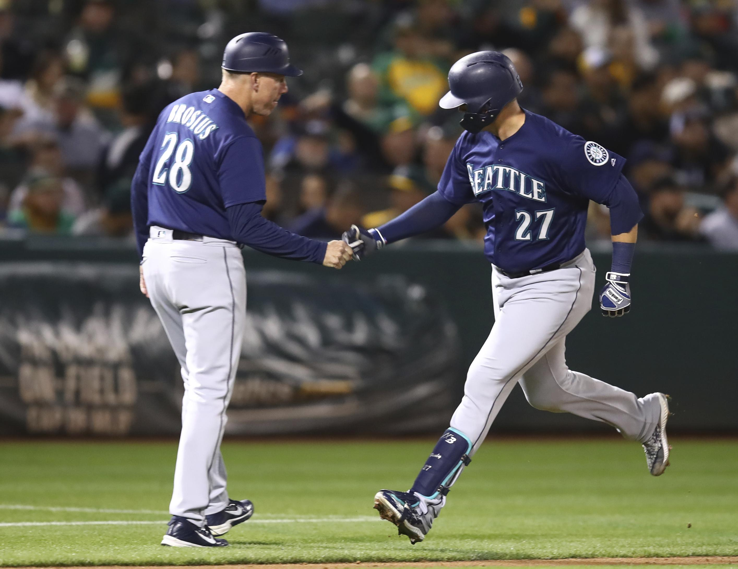 cb5ed6f62 Seattle s Ryon Healy is congratulated by third-base coach Scott Brosius  after hitting a two