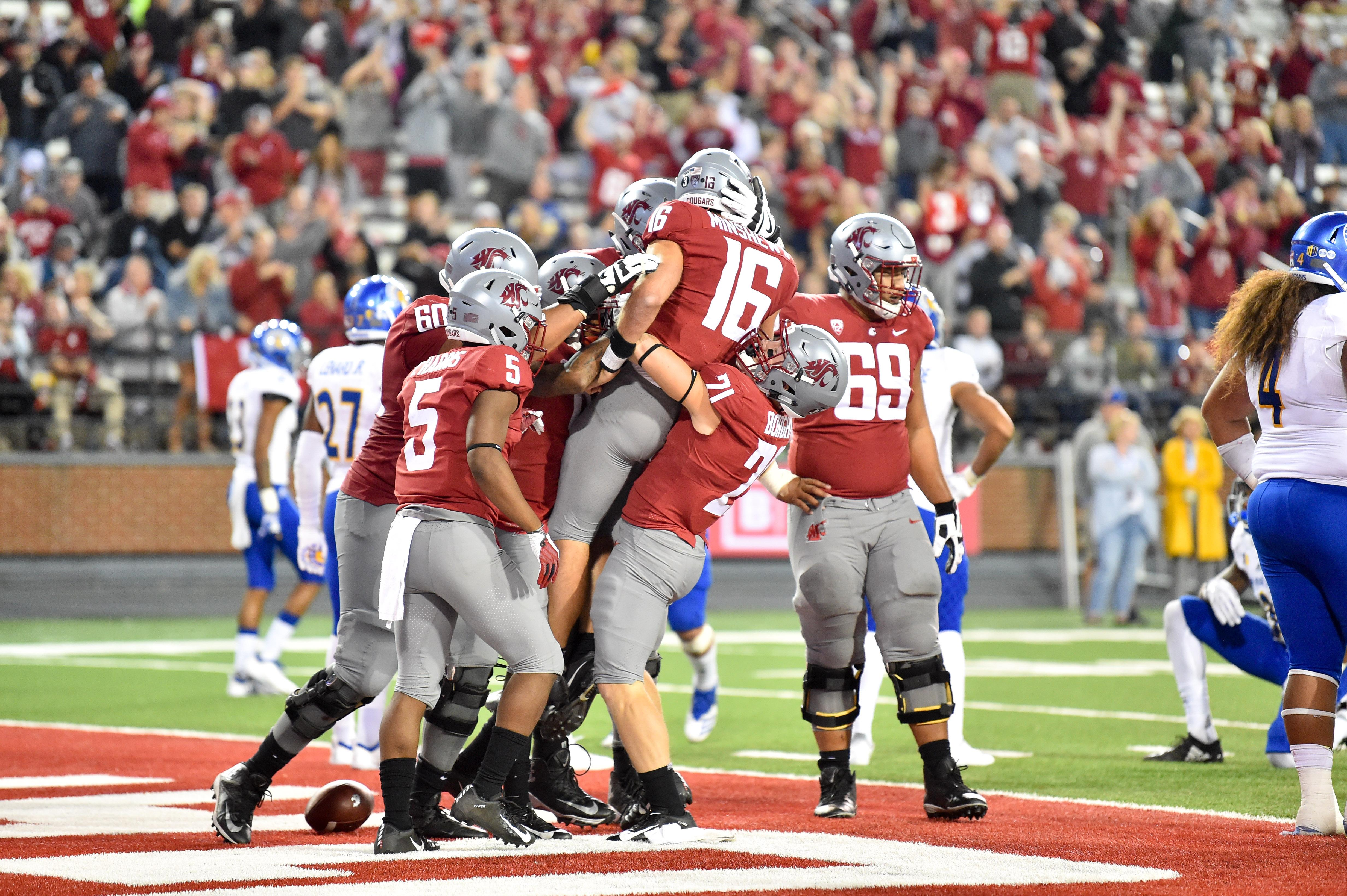 Washington State Cougars quarterback Gardner Minshew (16) is mobbed by  teammates after he ran cea5a109c