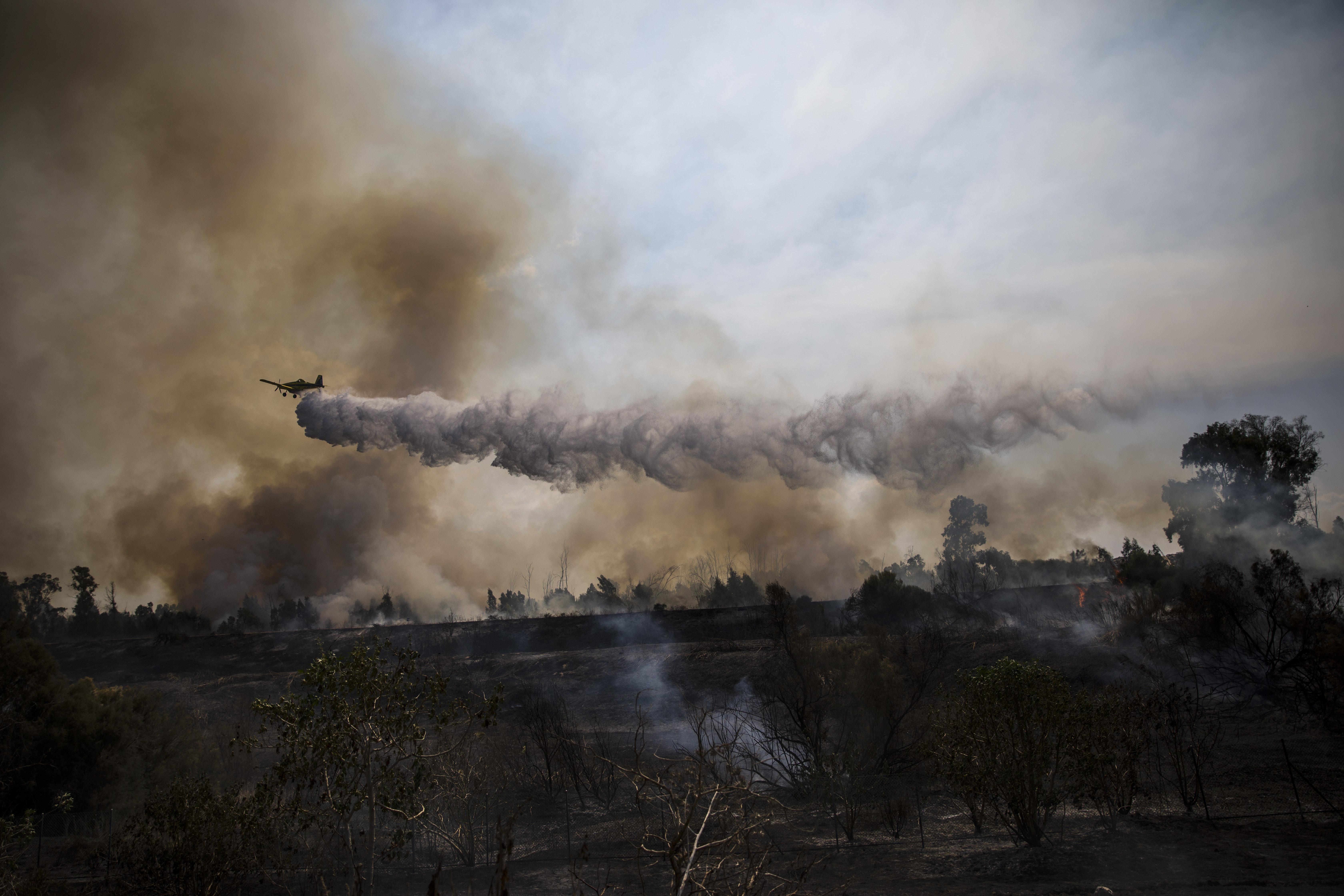 A firefighting plane passes over a fire started by a balloon with attached  burning cloth launched