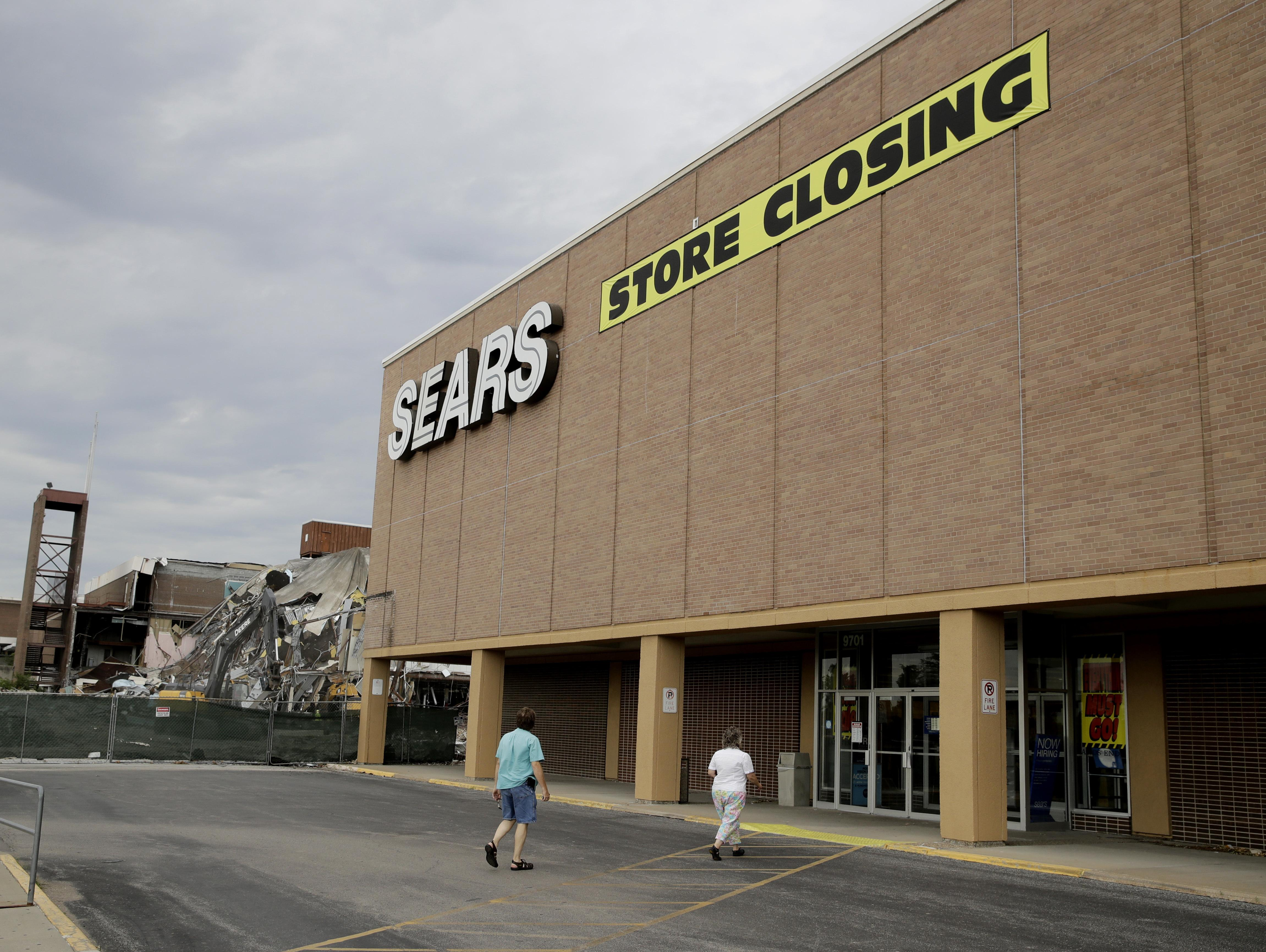 b62061a793 People walk into a Sears store slated for closing that is next to a mall  that