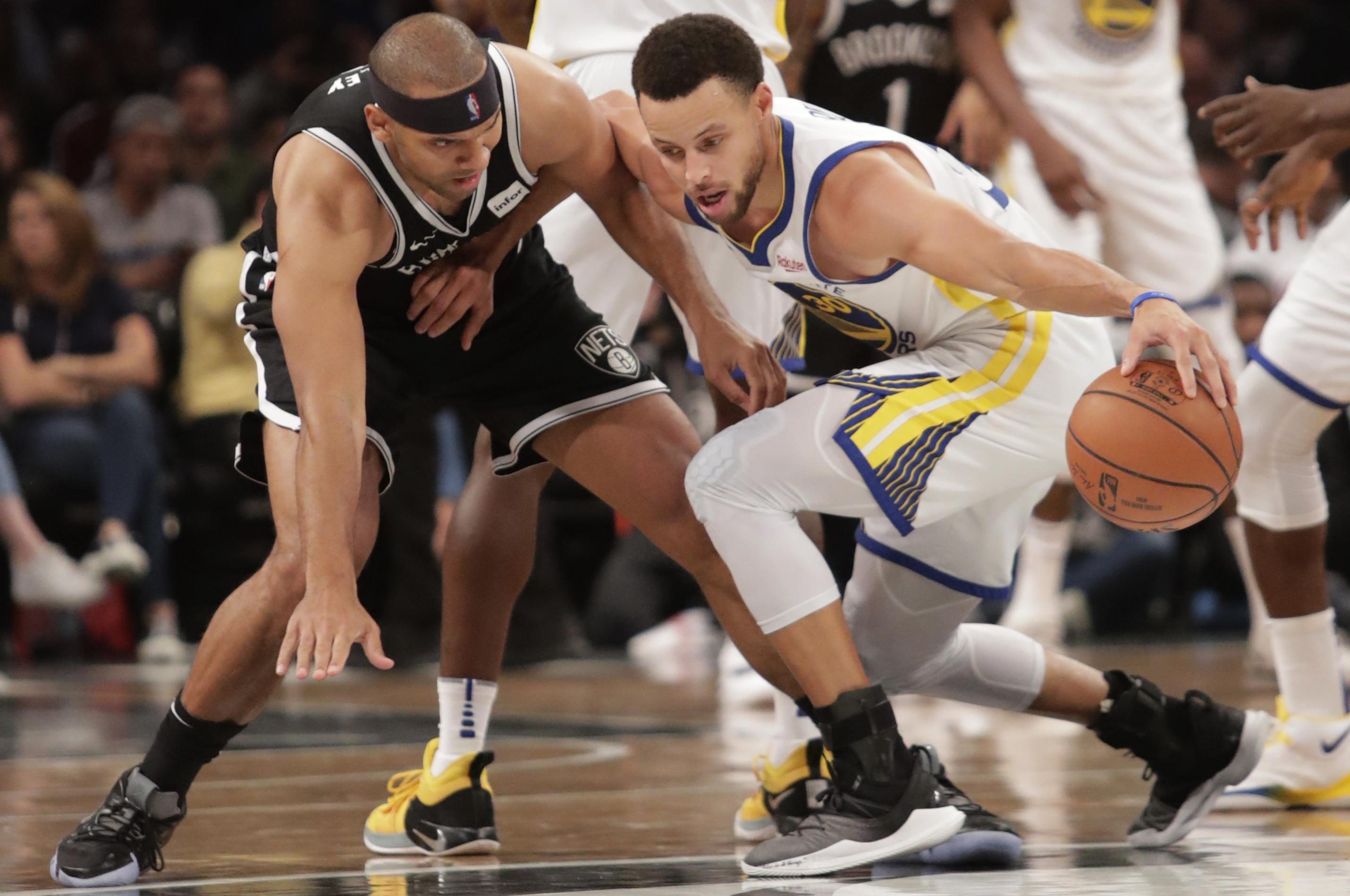 21ca8e66a46 Golden State Warriors' Stephen Curry, right, protects the ball from  Brooklyn Nets'