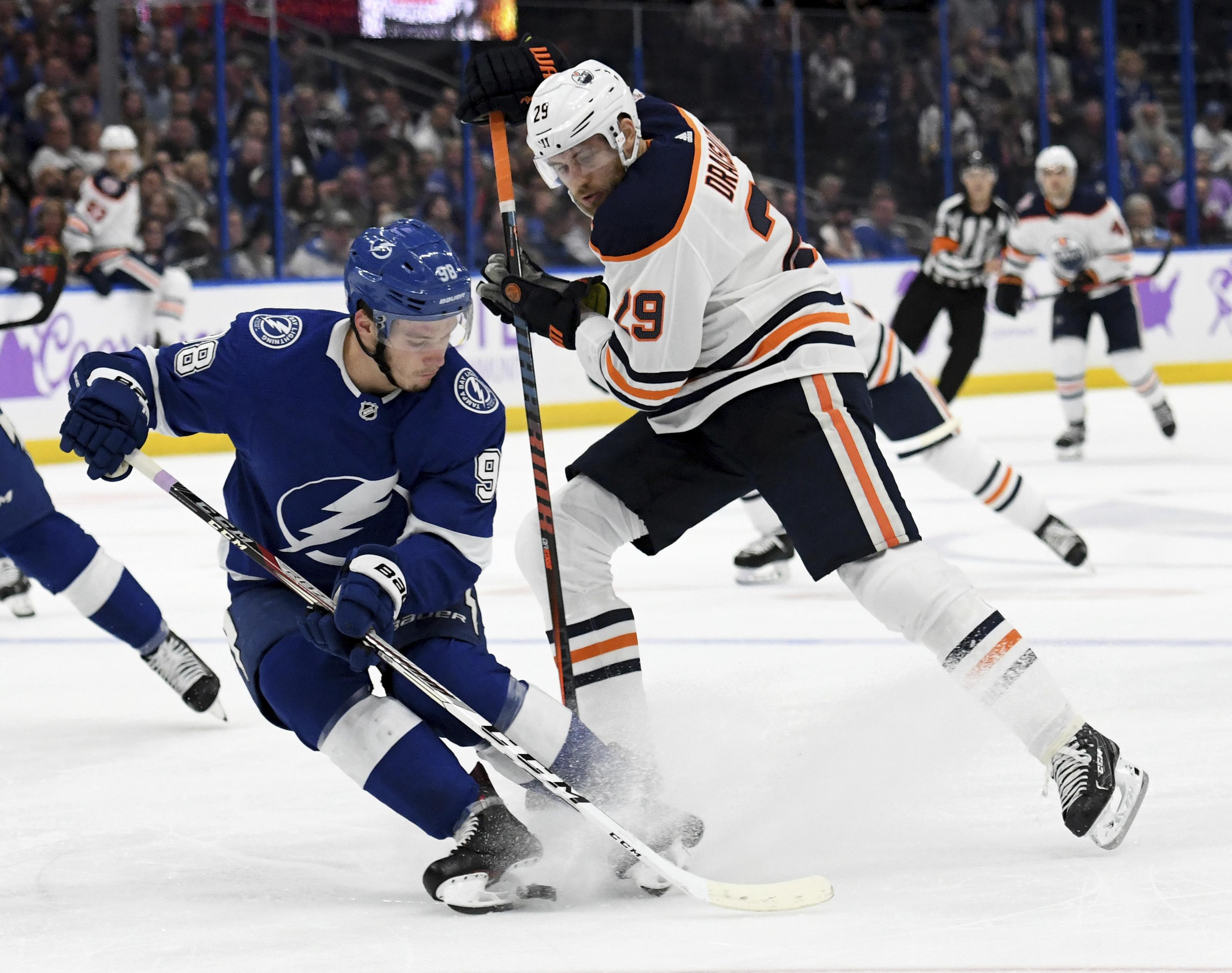 05e62952e5b Tampa Bay Lightning defenseman Mikhail Sergachev takes the puck from  Edmonton Oilers center Leon Draisaitl during