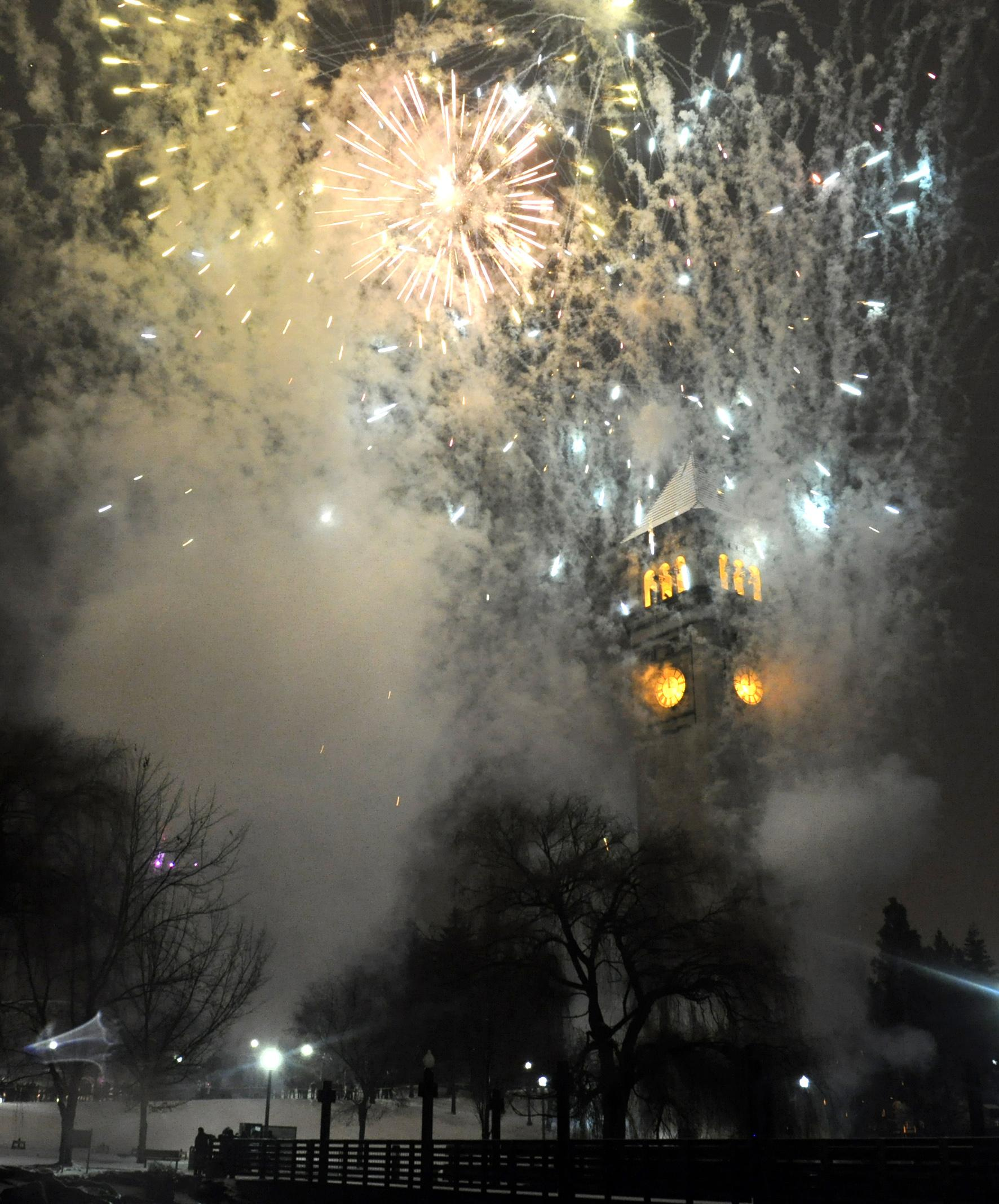 fireworks burst over the riverfront park clocktower as 2009 turns to 2010 in spokane