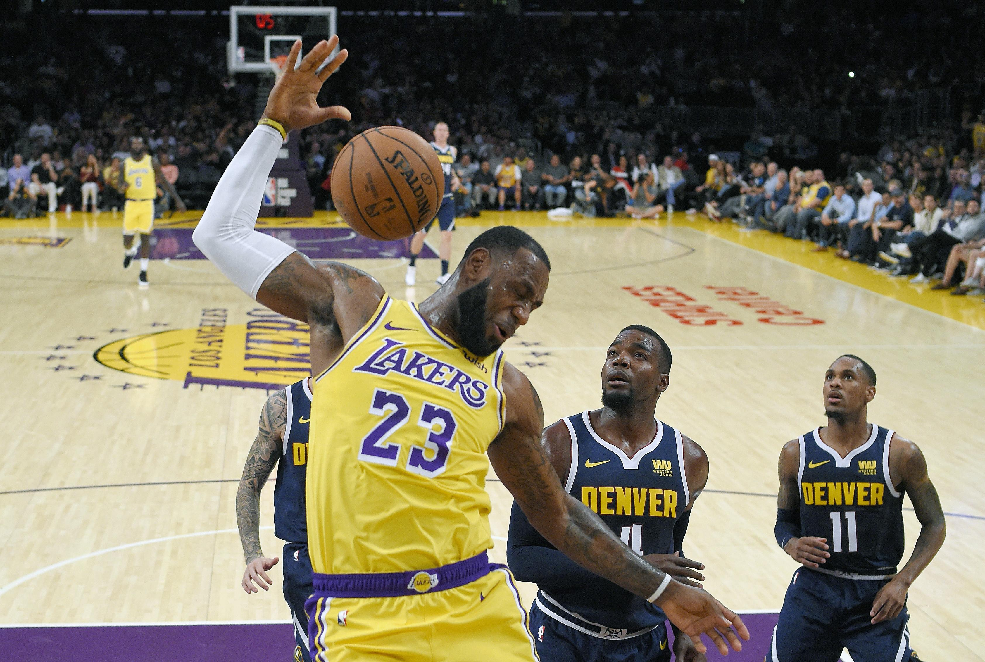 49904fca557 Los Angeles Lakers forward LeBron James, left, follows through on a dunk as  Denver