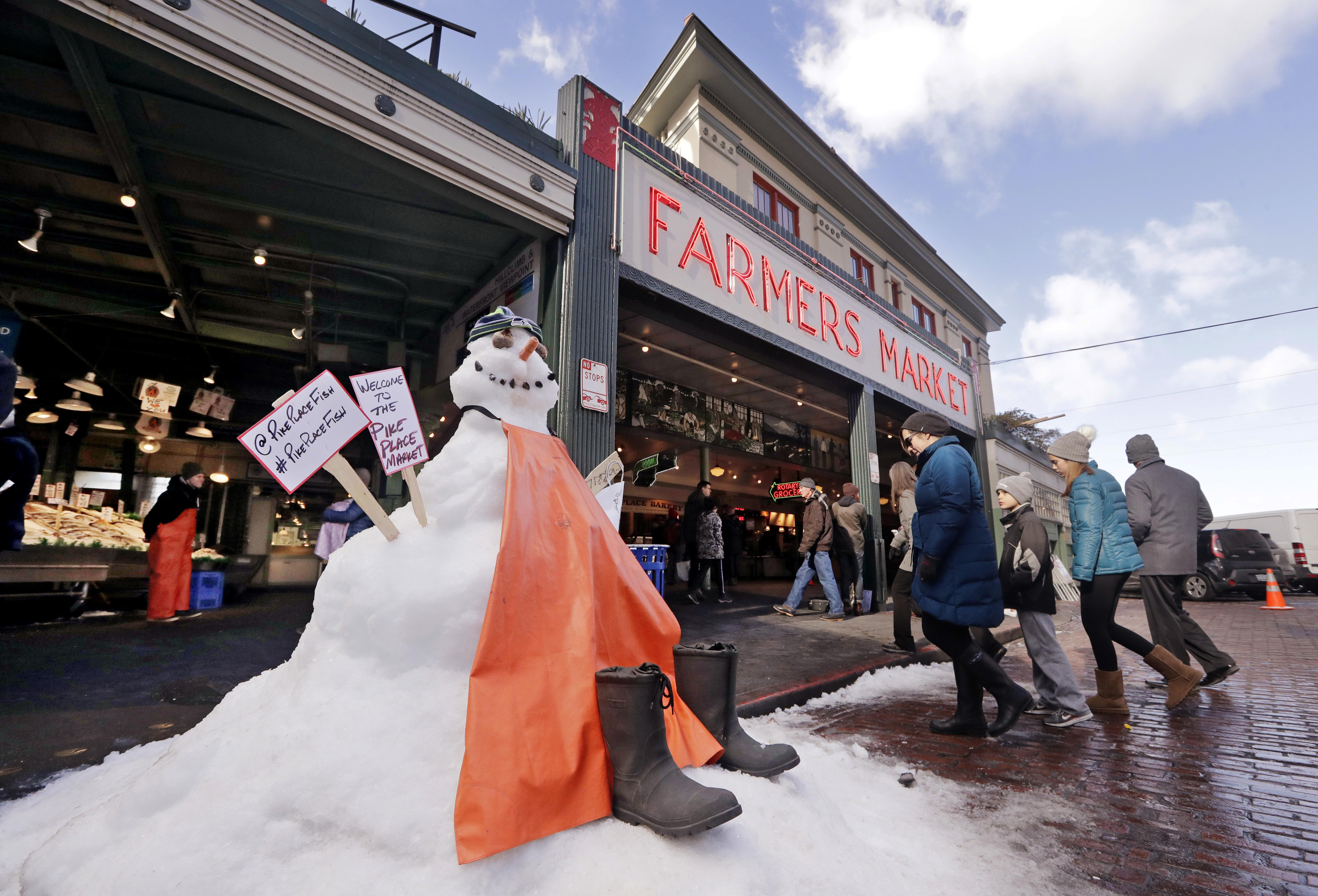 A Snow Sculpture Is Dressed As The Fish Mongers Working Behind People Walk Into