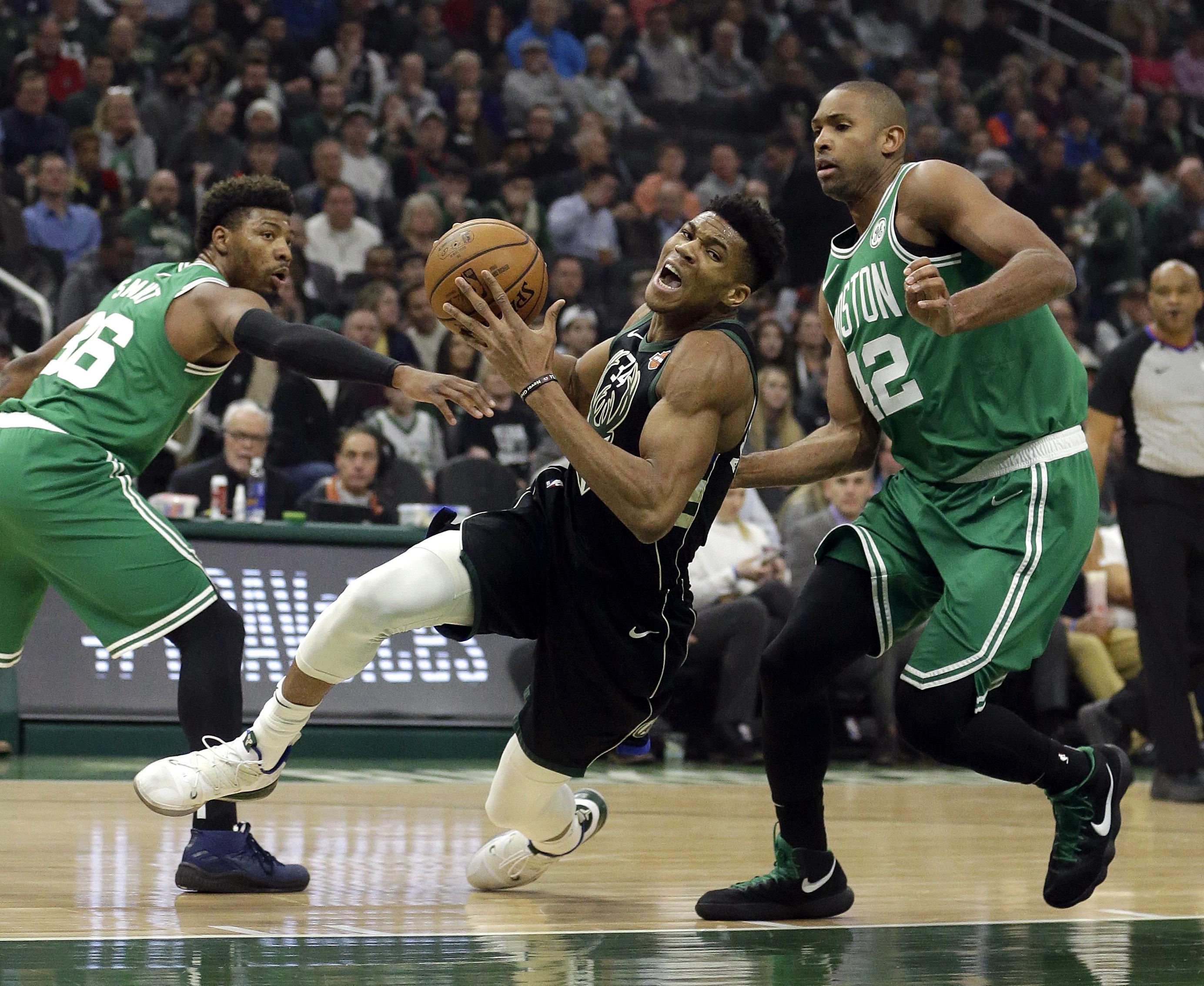 Bucks forward Giannis Antetokounmpo falls to the floor while defended by  Boston Celtics  Al Horford f3d9161d9