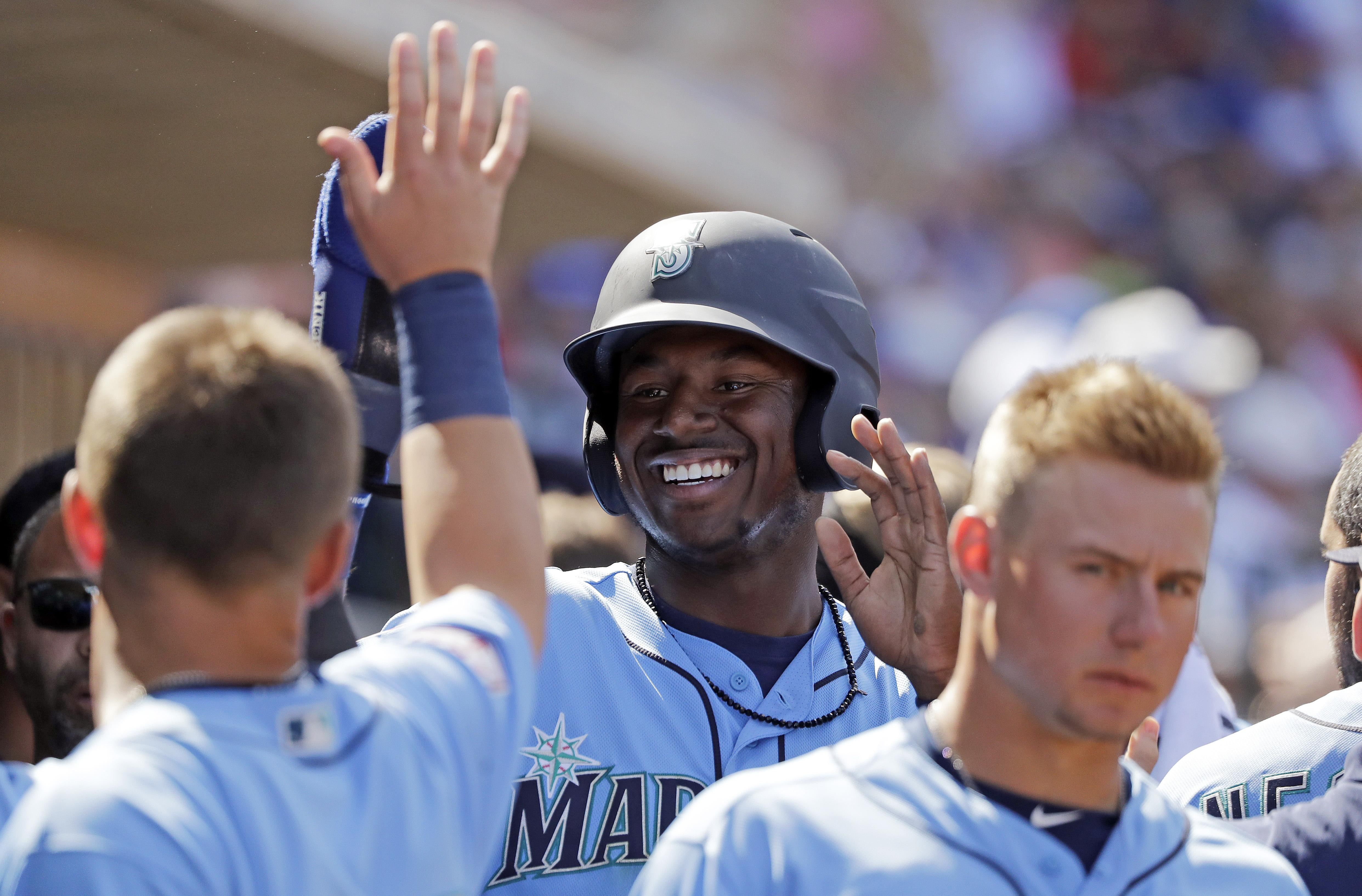 97551c04a1ea25 Seattle's Kyle Lewis is congratulated after scoring against the Chicago  Cubs during a spring training game