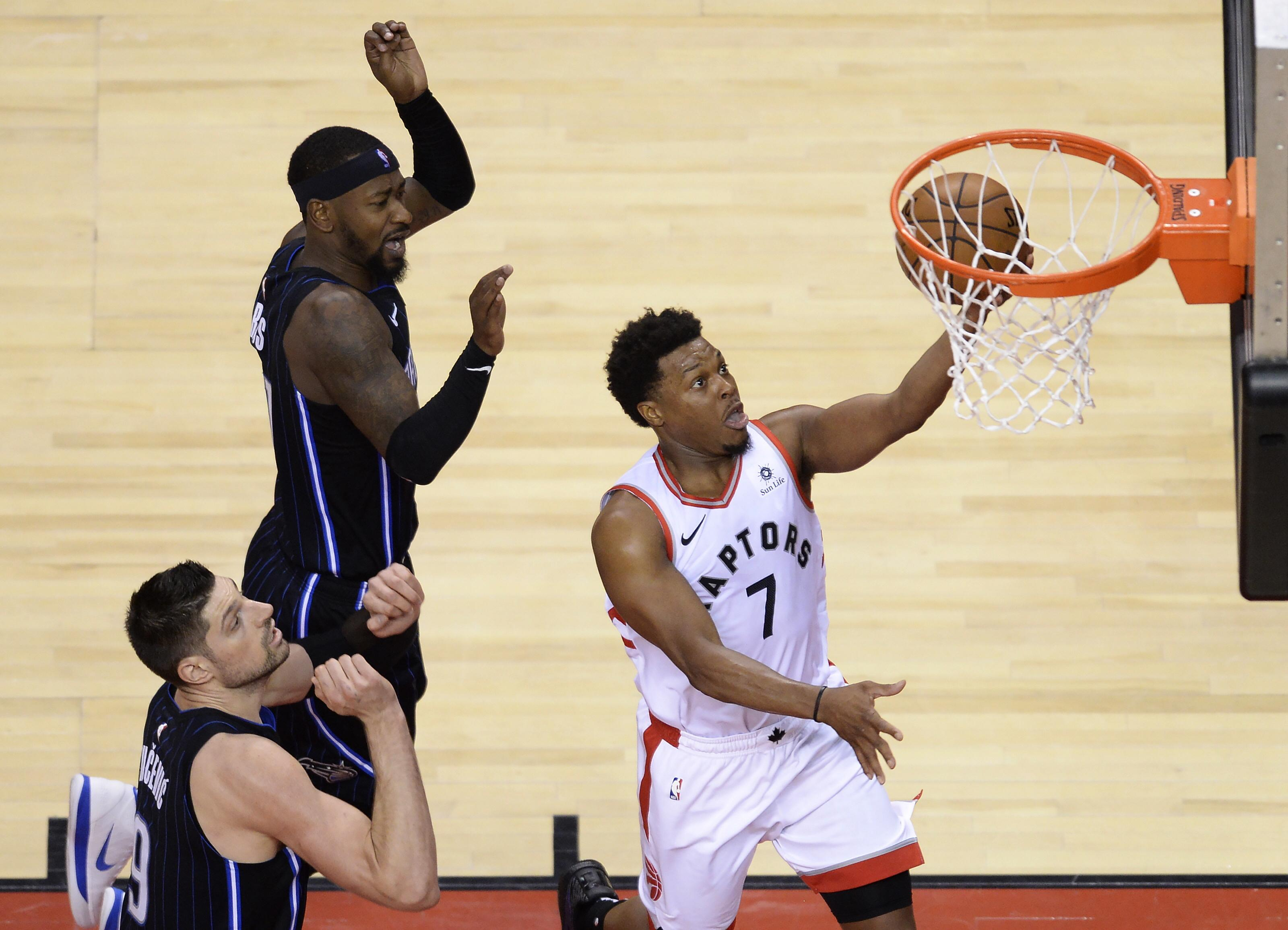 ffc591902eb0 Toronto Raptors guard Kyle Lowry (7) scores past Orlando Magic center  Nikola Vucevic (