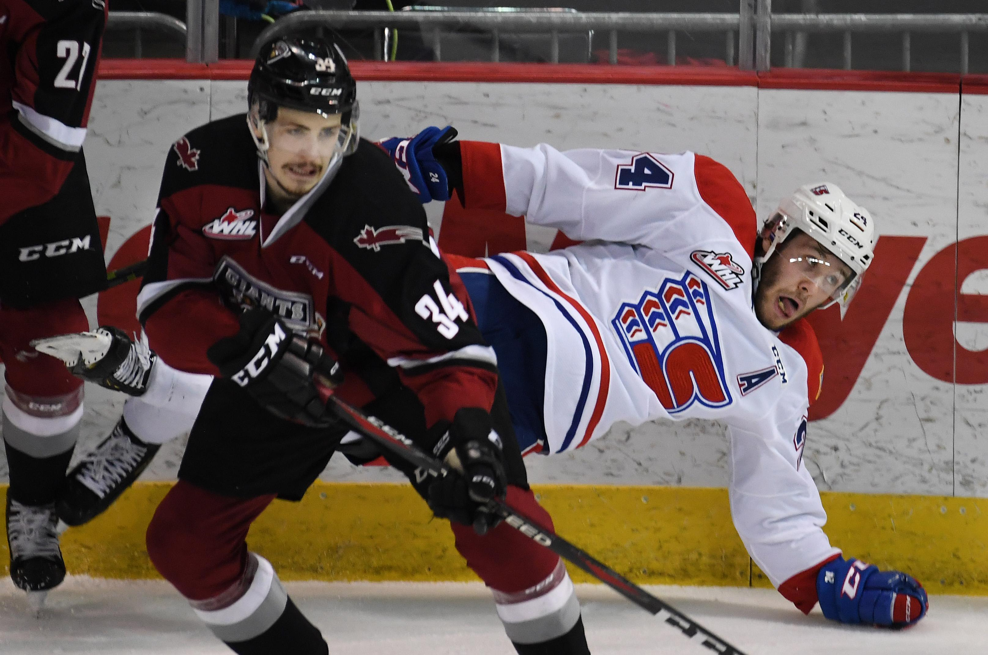 d6fc7d021 Spokane Chiefs forward Ty Smith falls after being checked on the boards by  Vancouver Giants forward