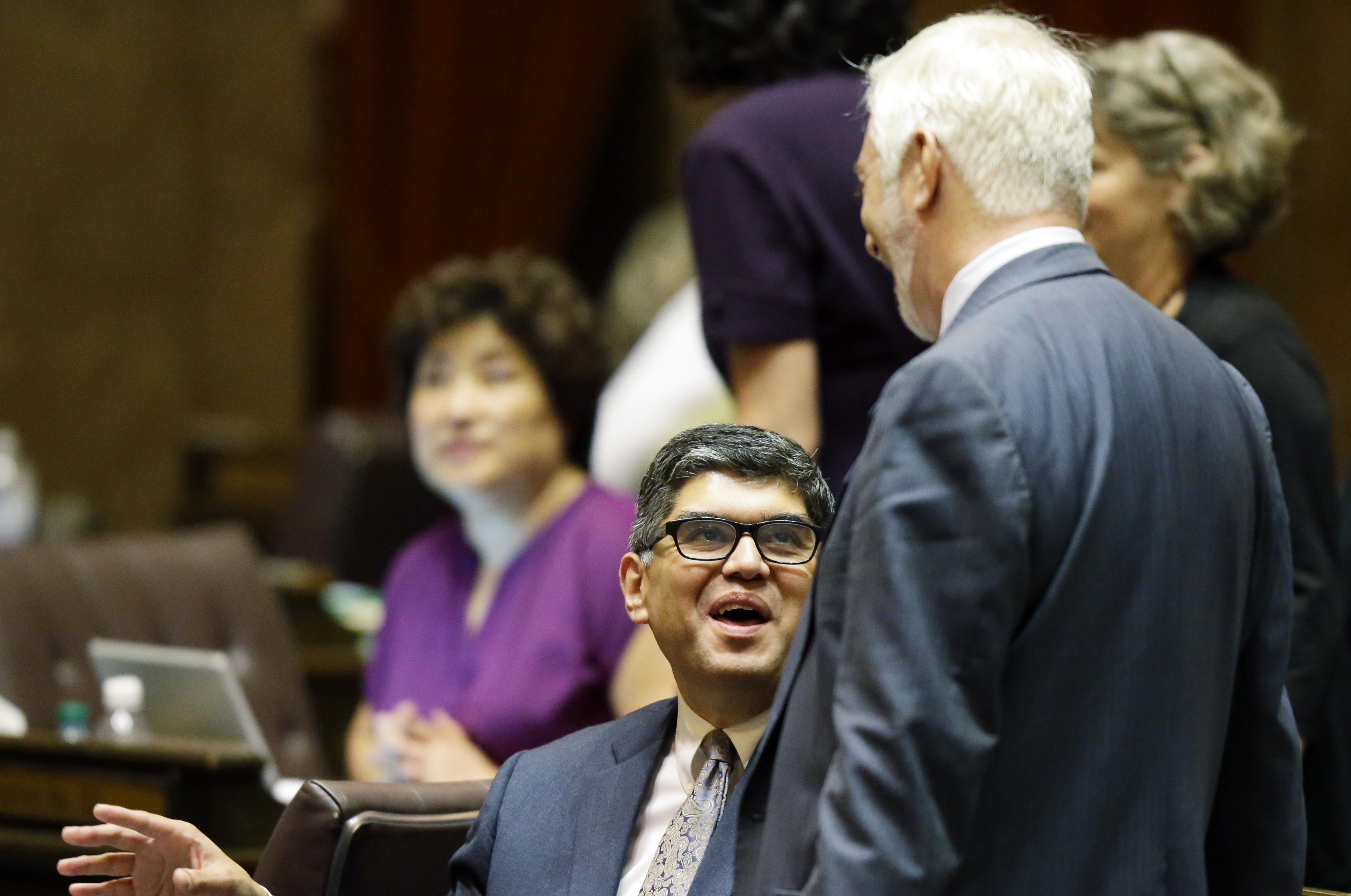 Rep. Javier Valdez and Rep. Gerry Pollet talk after passage os the paid family leave program